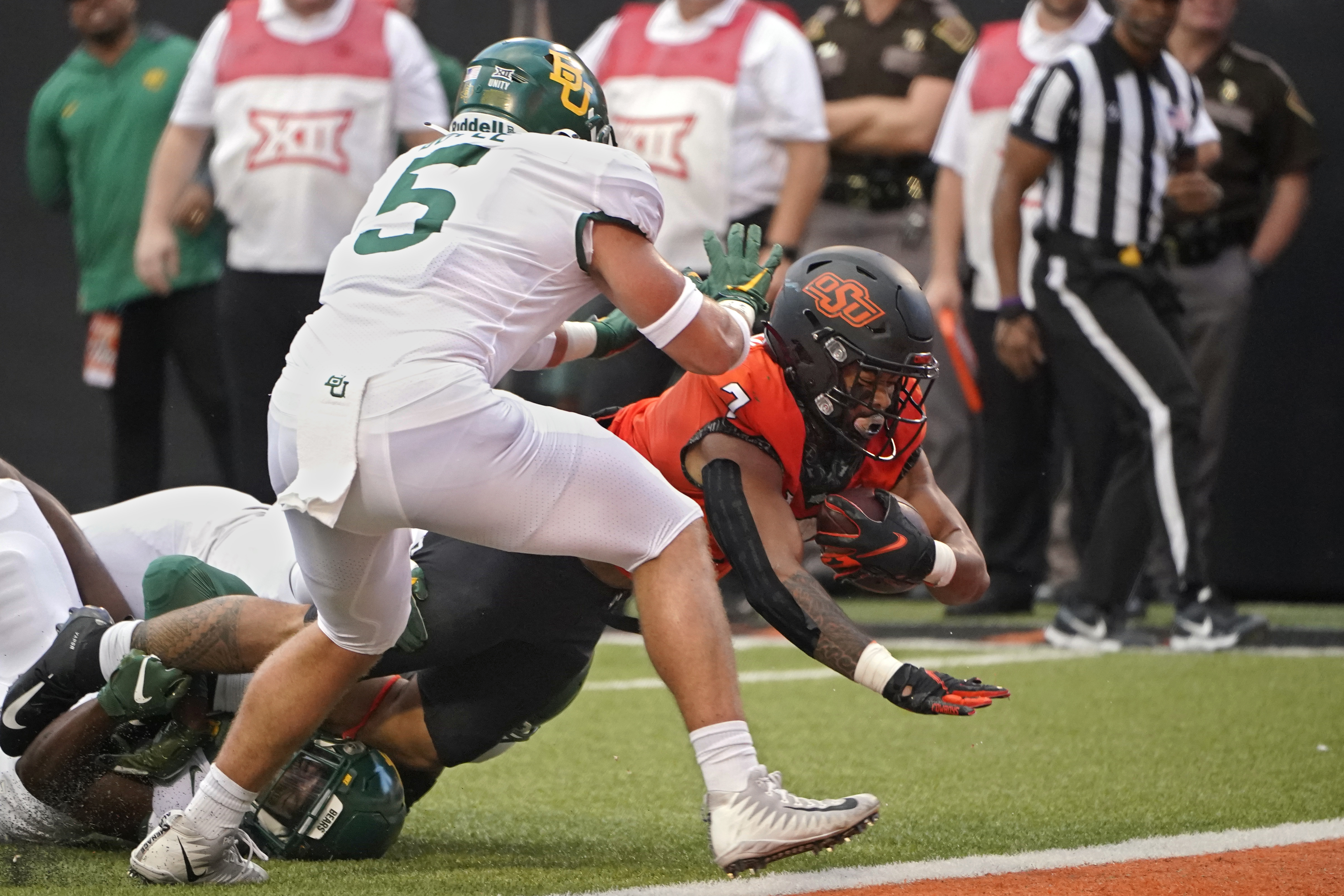 Oklahoma State running back Jaylen Warren (7) dives into the end zone in front of Baylor's Dillon Doyle (5) for a touchdown.