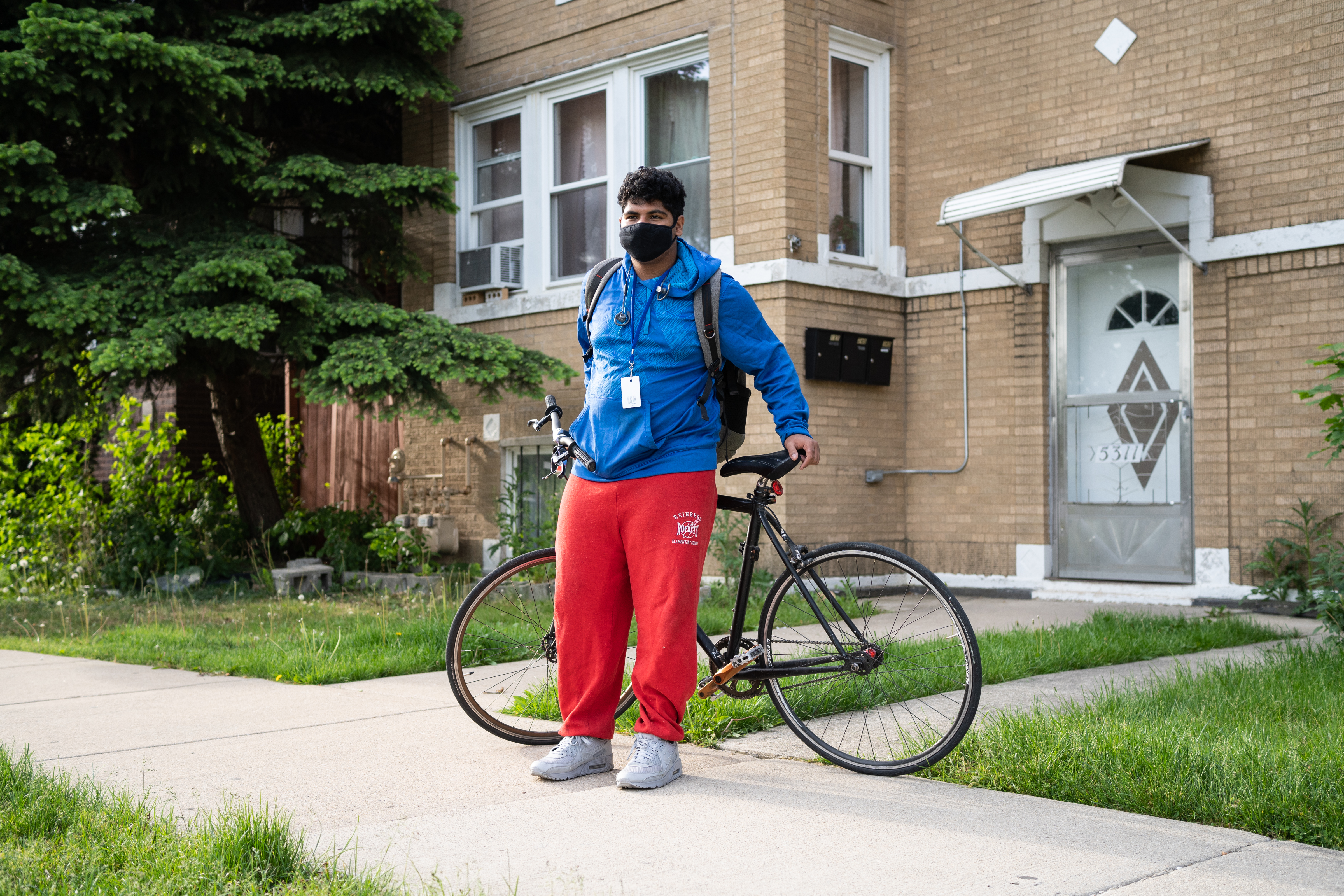 A young man, wearing a blue jacket, protective mask, and red track pants, poses for a portrait with his bike before riding to his high school.