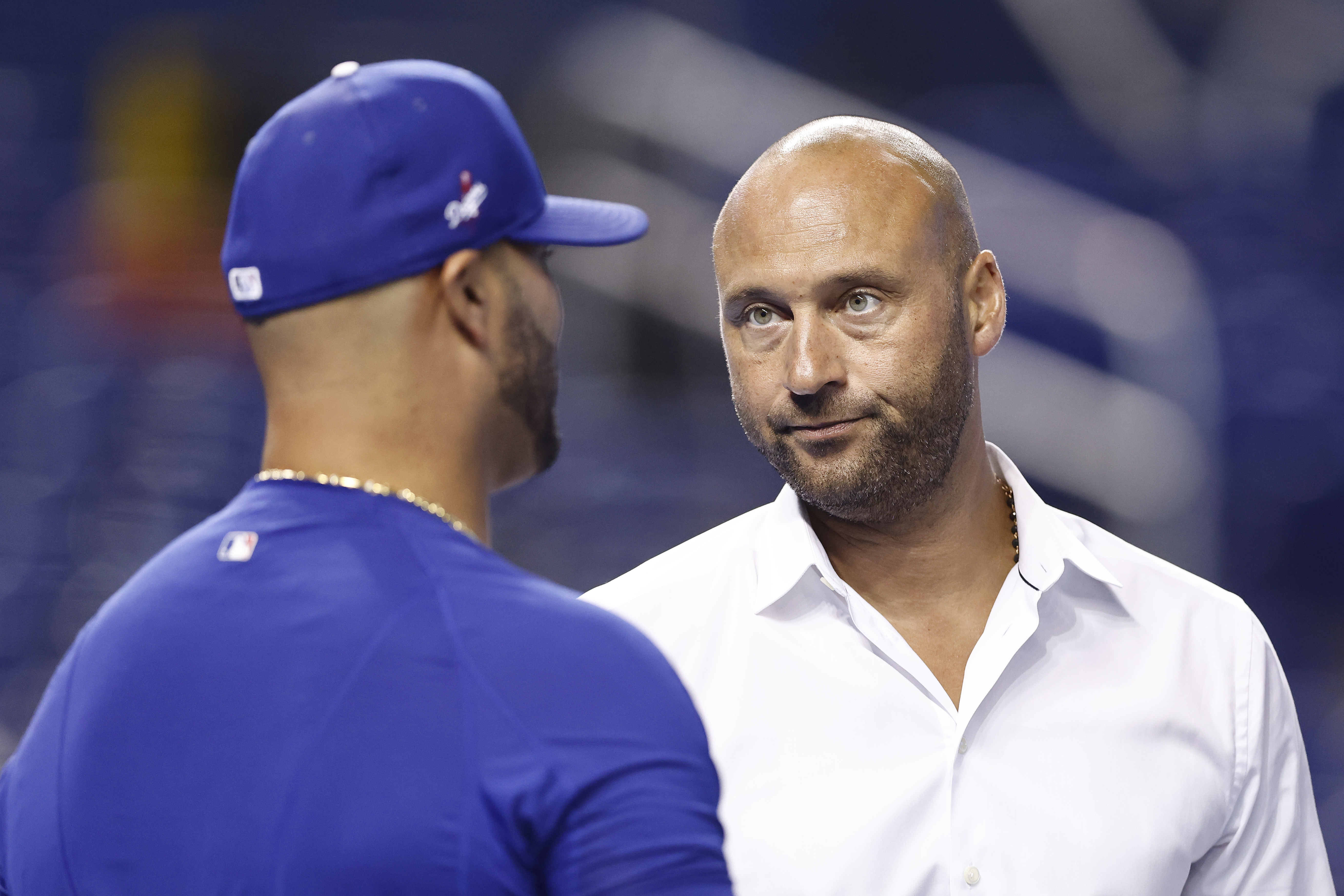 CEO Derek Jeter of the Miami Marlins talks with Albert Pujols #55 of the Los Angeles Dodgers during batting practice prior to the game at loanDepot park
