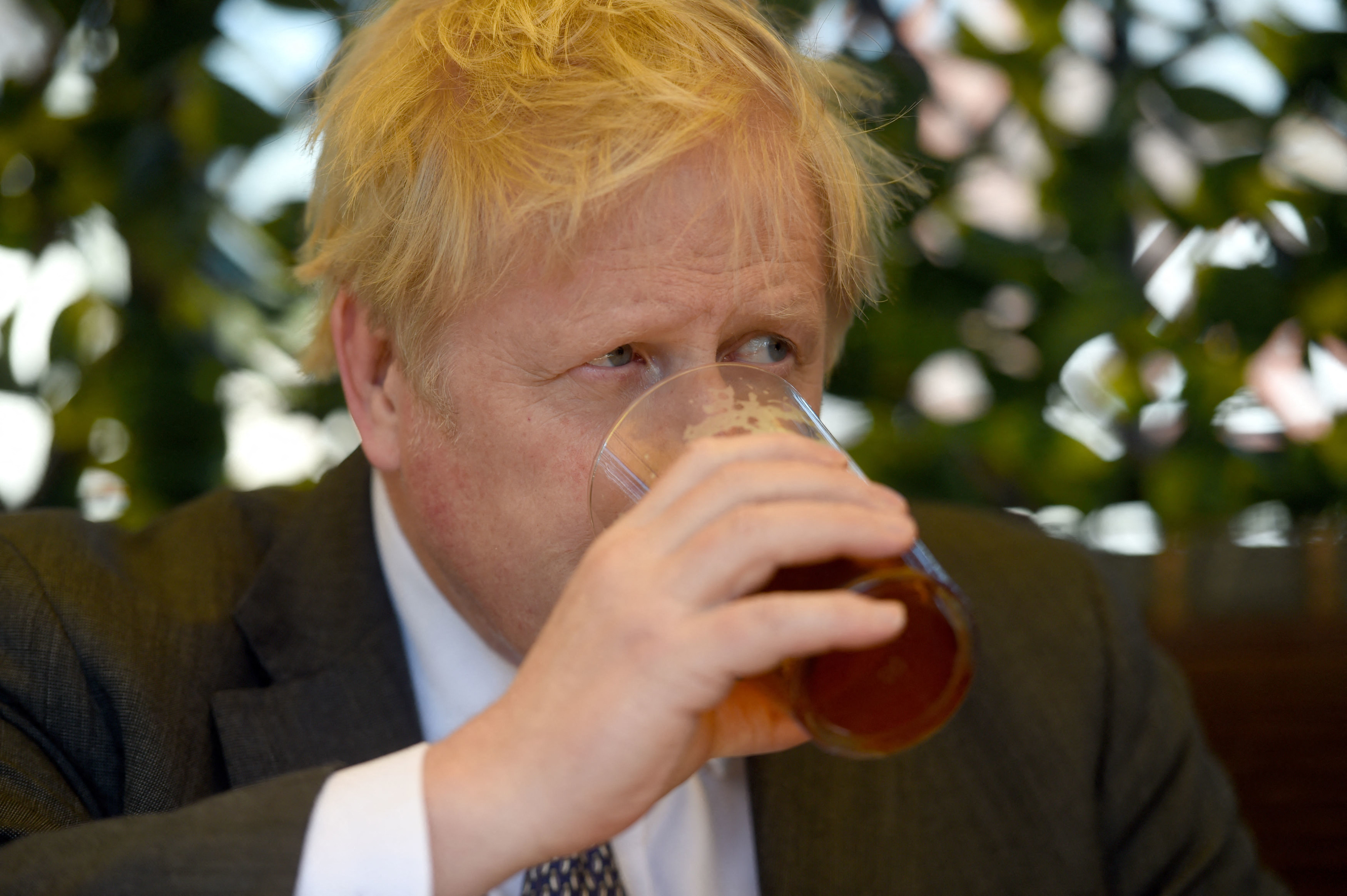 Boris Johnson sits drinking a pint of beer while wearing a suit