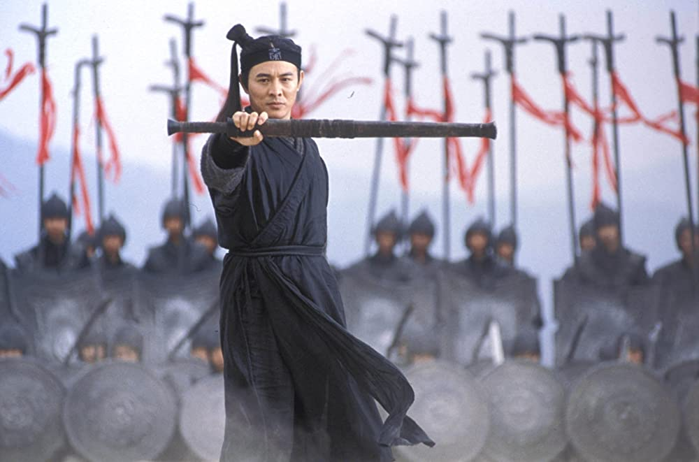 Jet Li stands with a sword in front of a group of warriors carrying standards and shields.