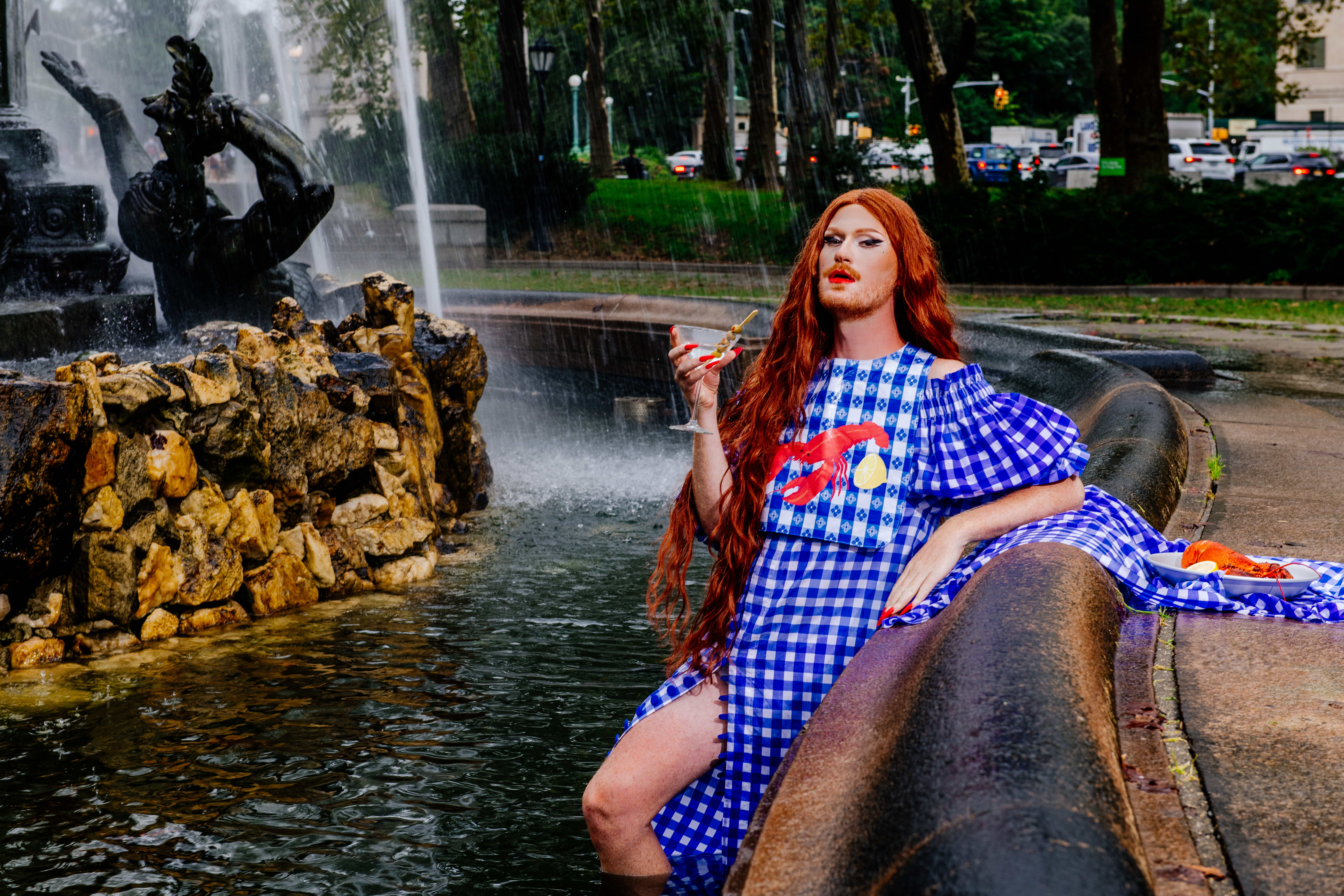 A drag queen wearing a gingham bib with a lobster motif and holding a martini lounges in a fountain