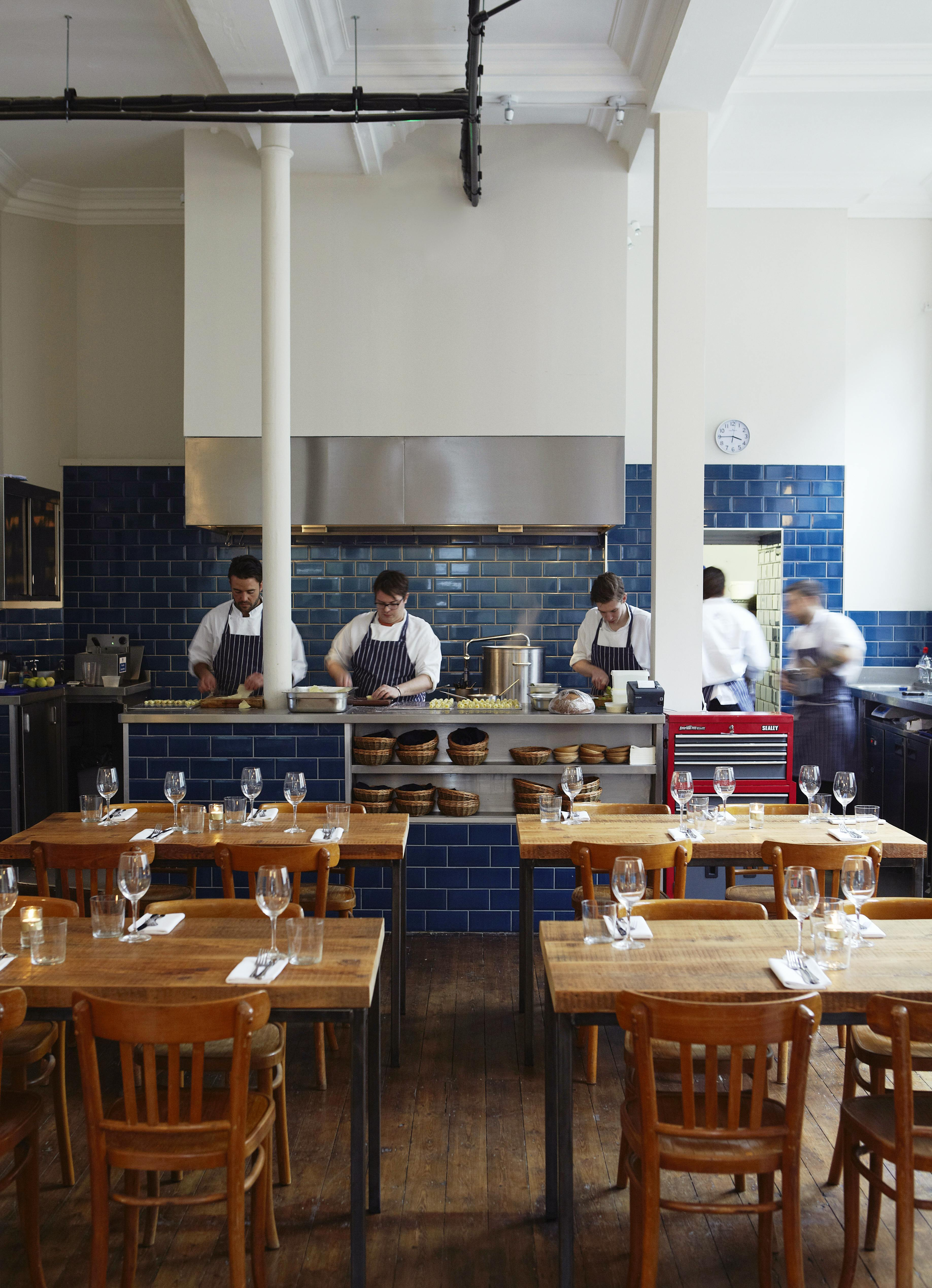 The open kitchen at The Clove Club in London, with chefs on a metal pass framed by blue tiles.