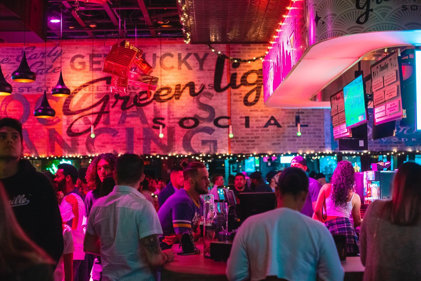 a neon-drenched nightclub with several dozen people hanging out by the bar