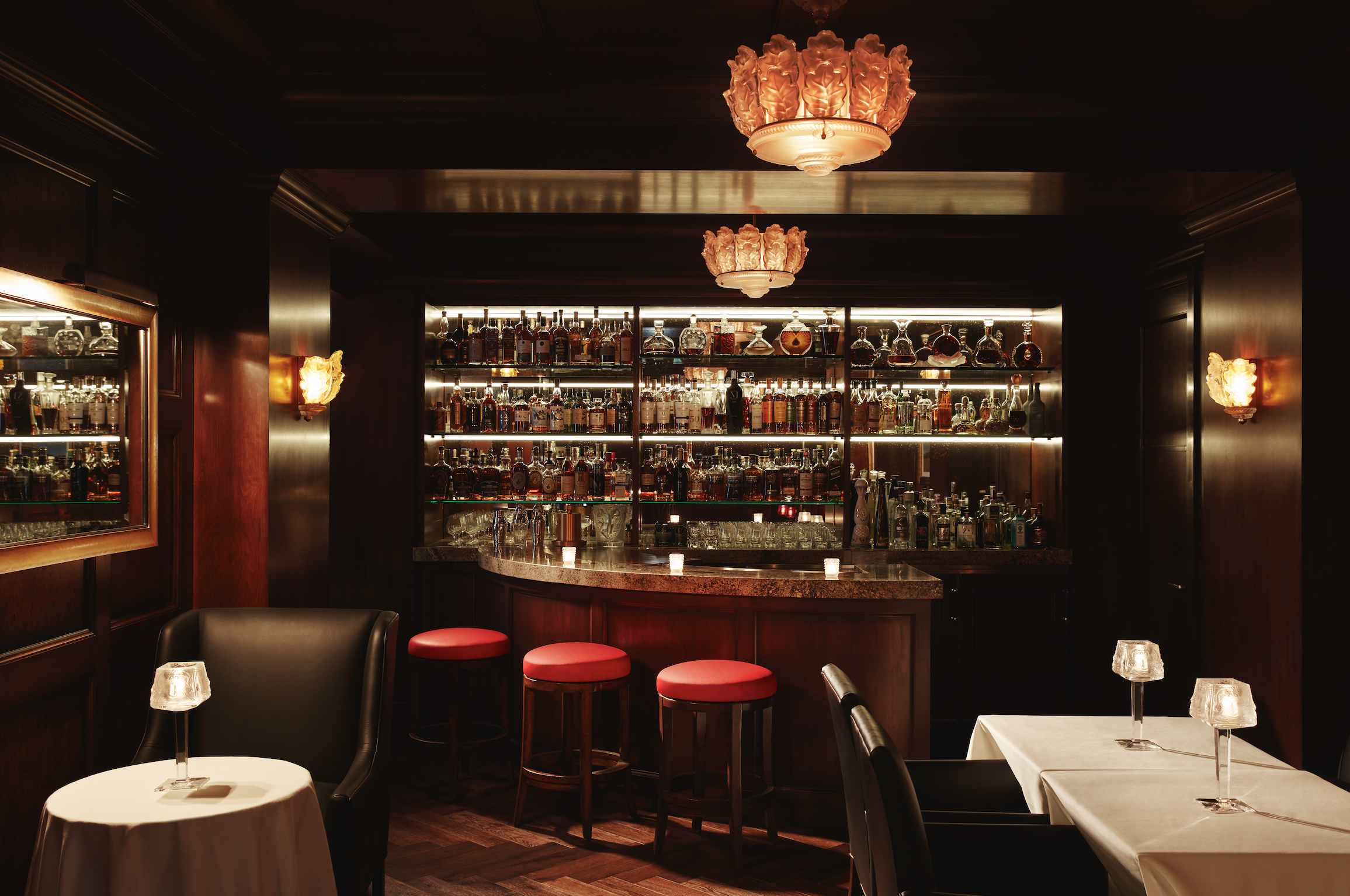 Maybourne's Cigar and Whiskey Lounge. with white tablecloth tables, red stools at a small bar with bottles in the back.