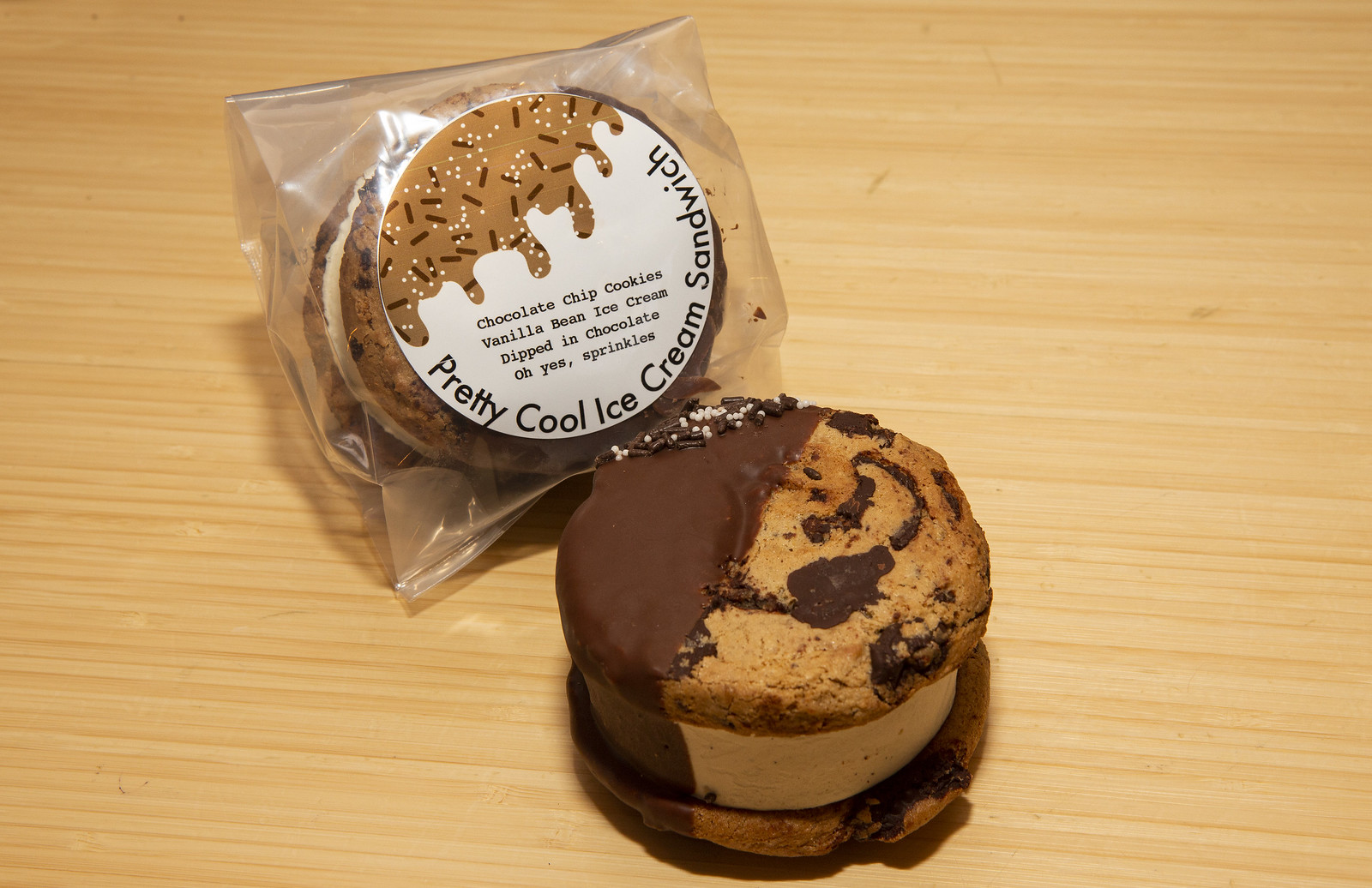 A packaged ice cream sandwich in plastic next to an ice cream sandwich with large cookies.