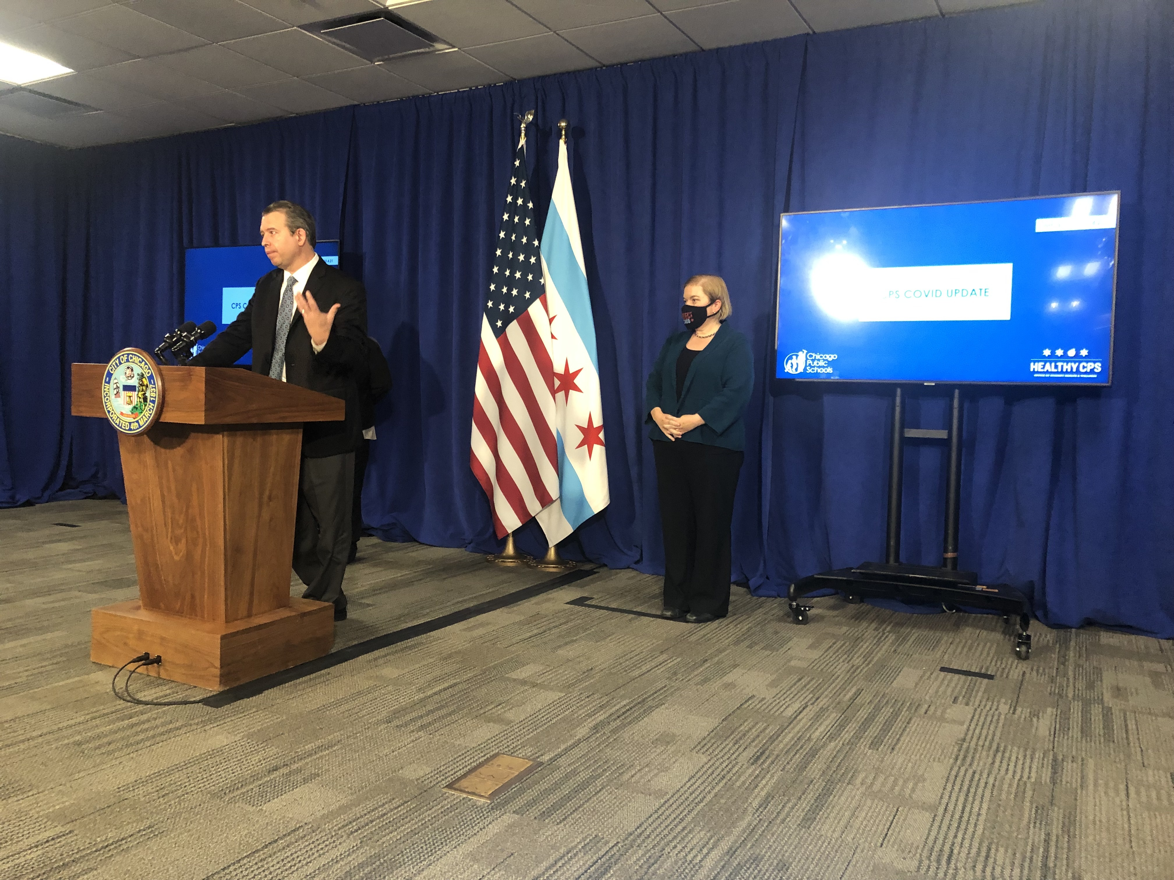 Standing at a podium in a suit and tie, Chicago Public Schools CEO Pedro Martinez explains the new quarantine rules alongside Dr. Allison Arwady, the city's top health official.