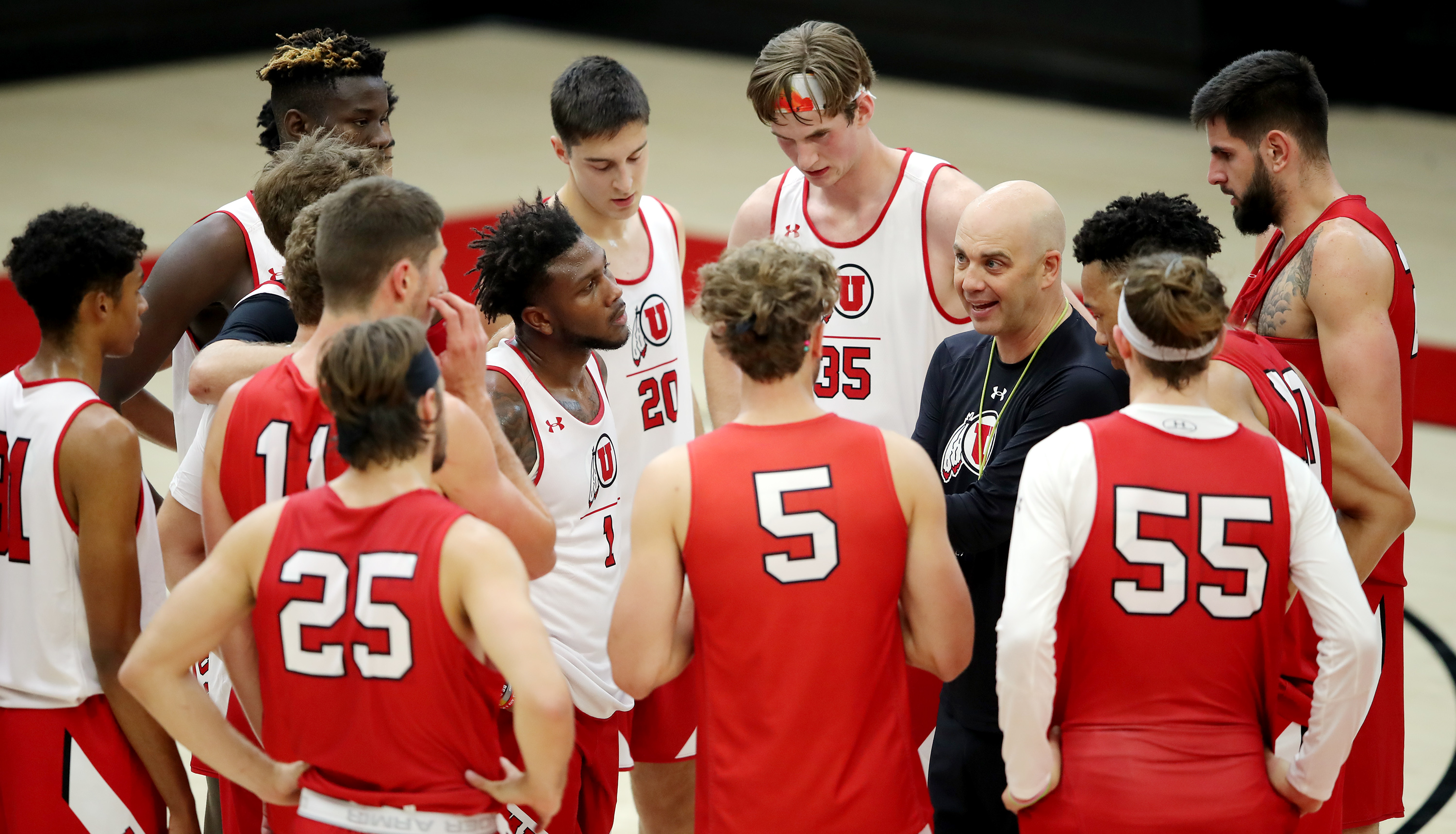Utah basketball coach Craig Smith talks to his players in a team huddle as the team opens camp on Tuesday, Sept. 28, 2021.