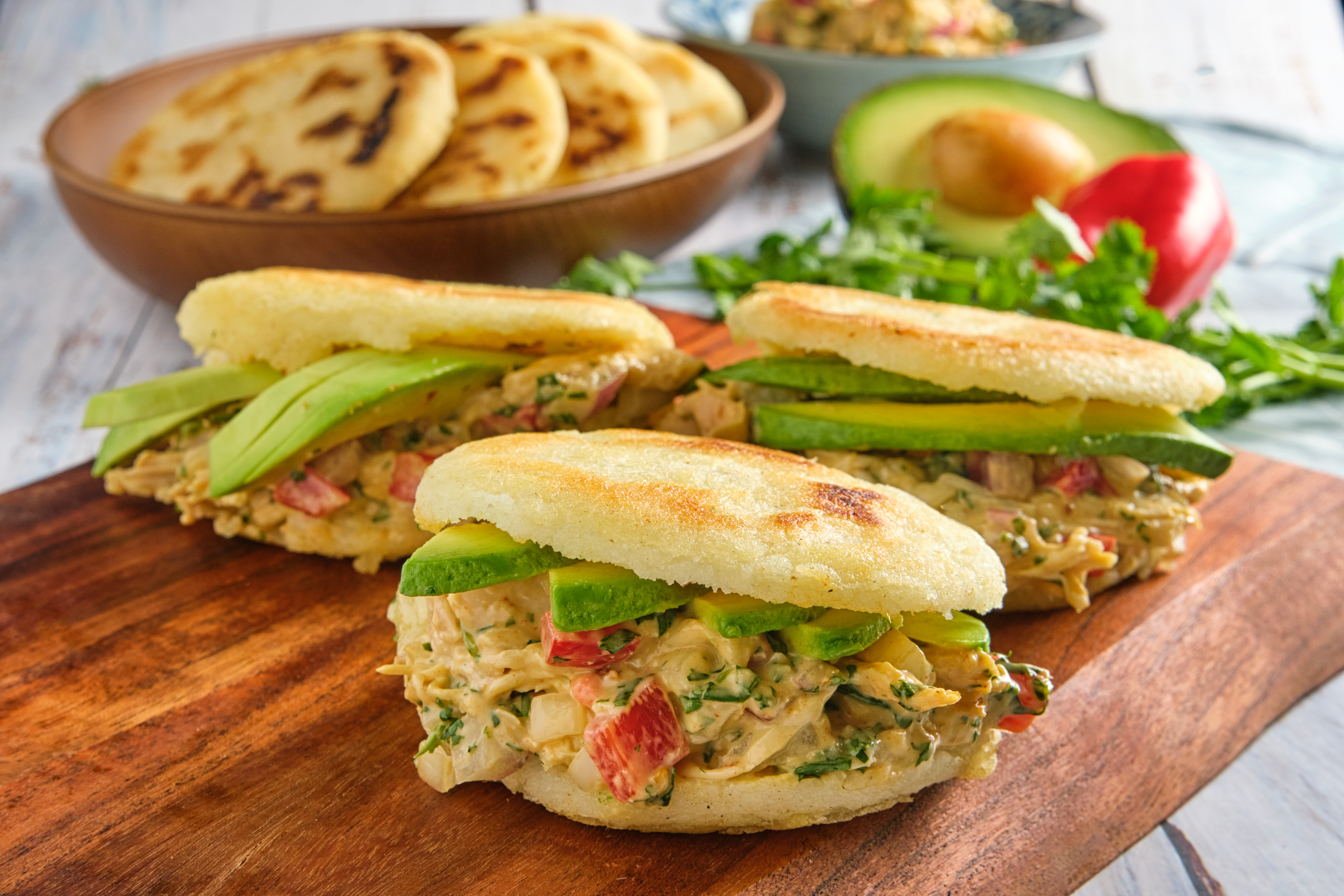 Three arepas sit on a wooden cutting board with a bowl of unstuffed arepas in the background.