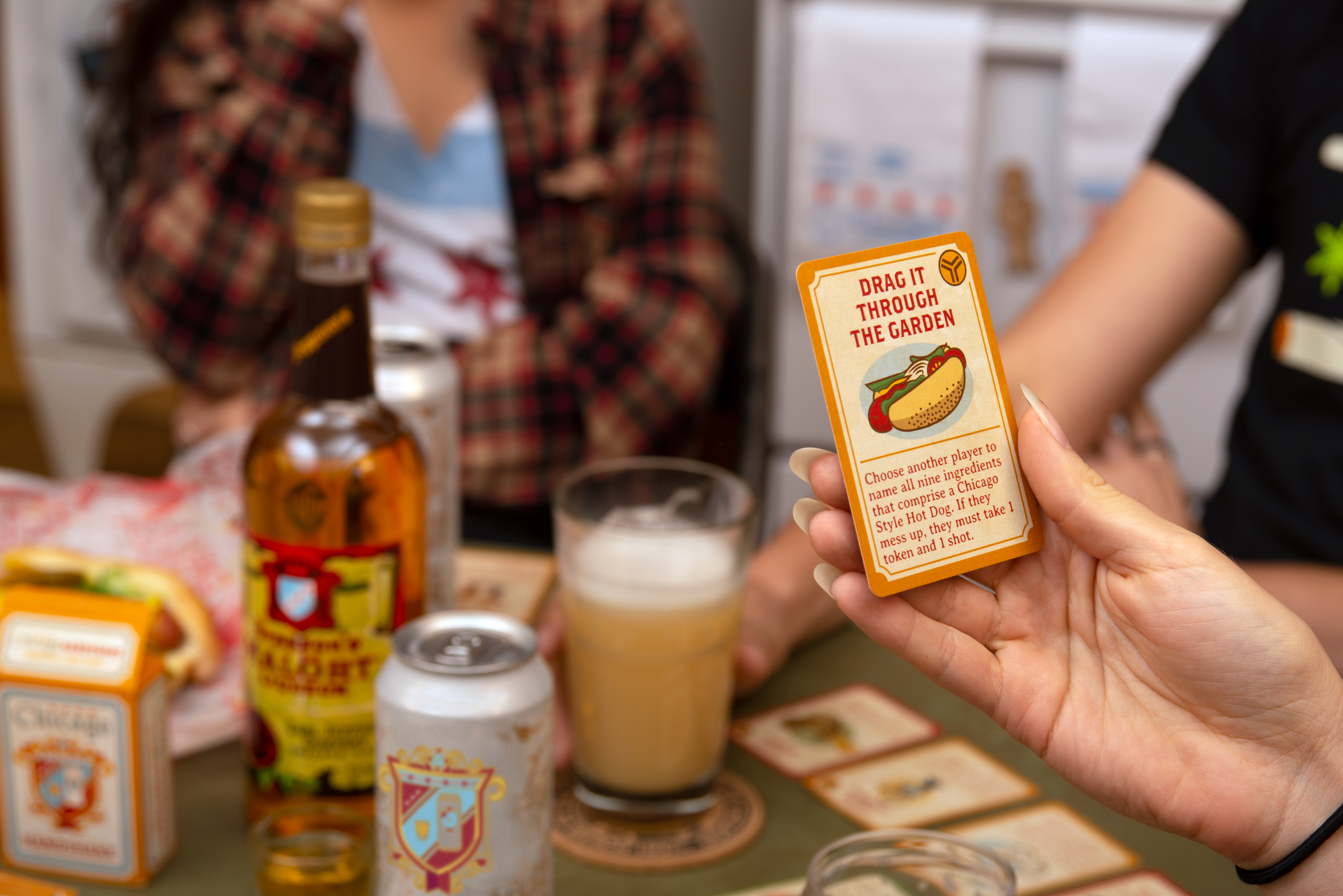 A person's hand holds a playing card with an illustration of a Chicago-style hot dog.