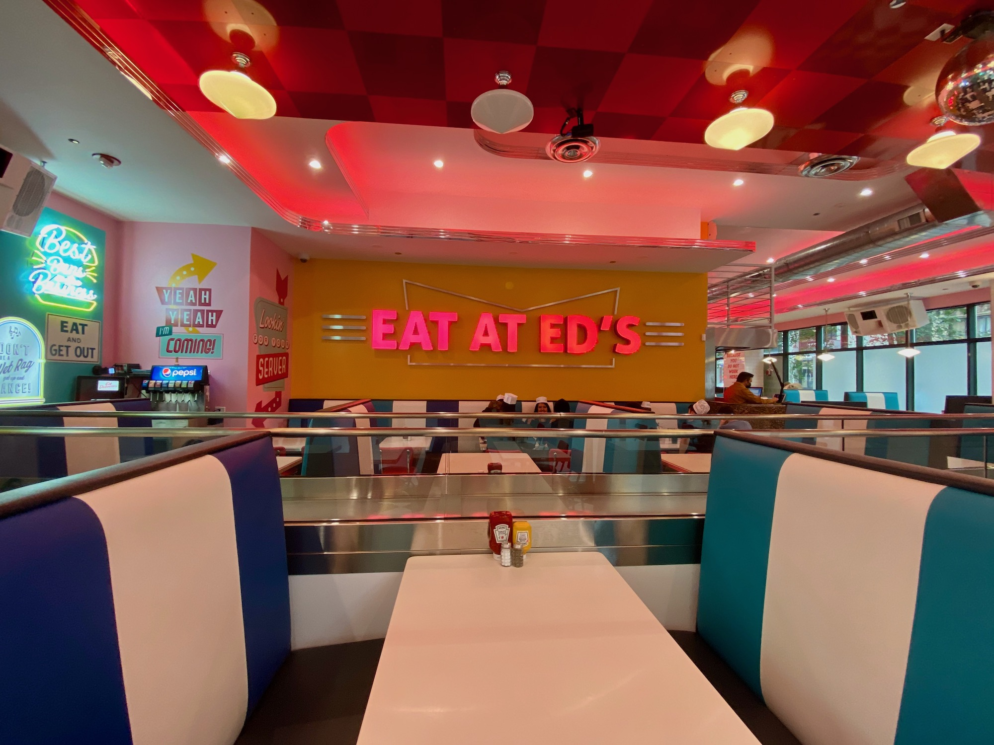 """blue and white striped diner booths in the foreground in front of a yellow wall with a pink neon sign that reads """"Eat at Ed's"""""""
