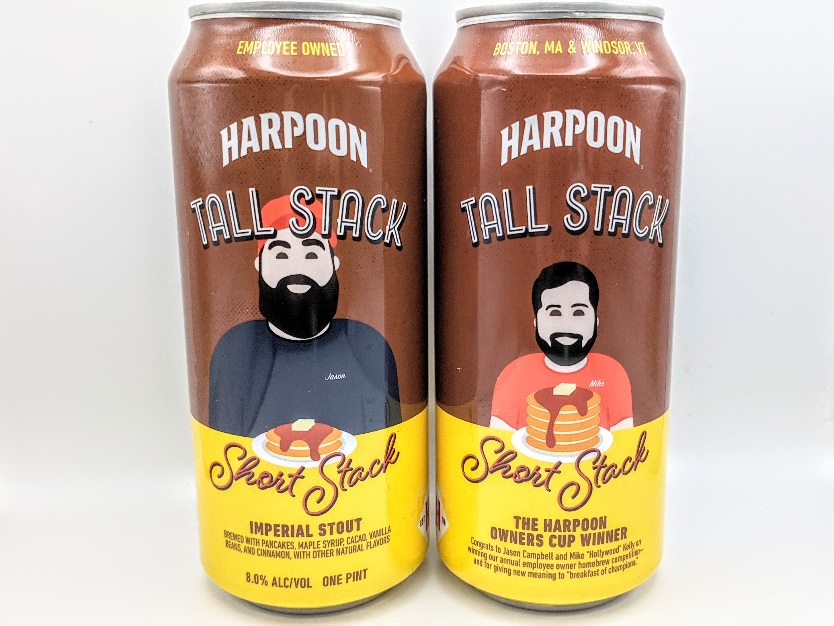 Two cans of beer stand next to each other on a white background, showing two sides of the pancake-themed label of the same beer.
