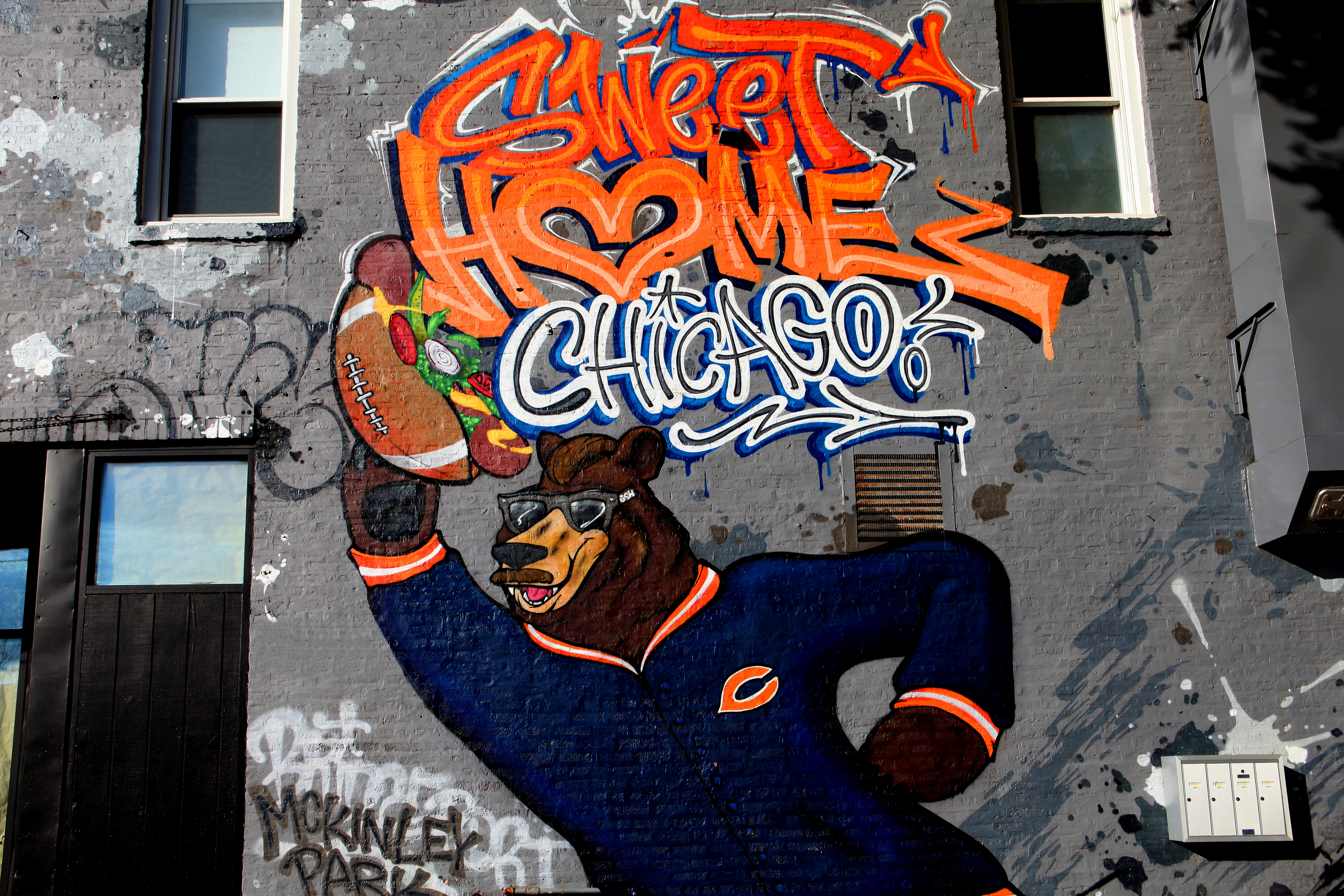 A mural of a brown bear in a navy blue Chicago Bears sweater holding a hot dog with a football for a bun