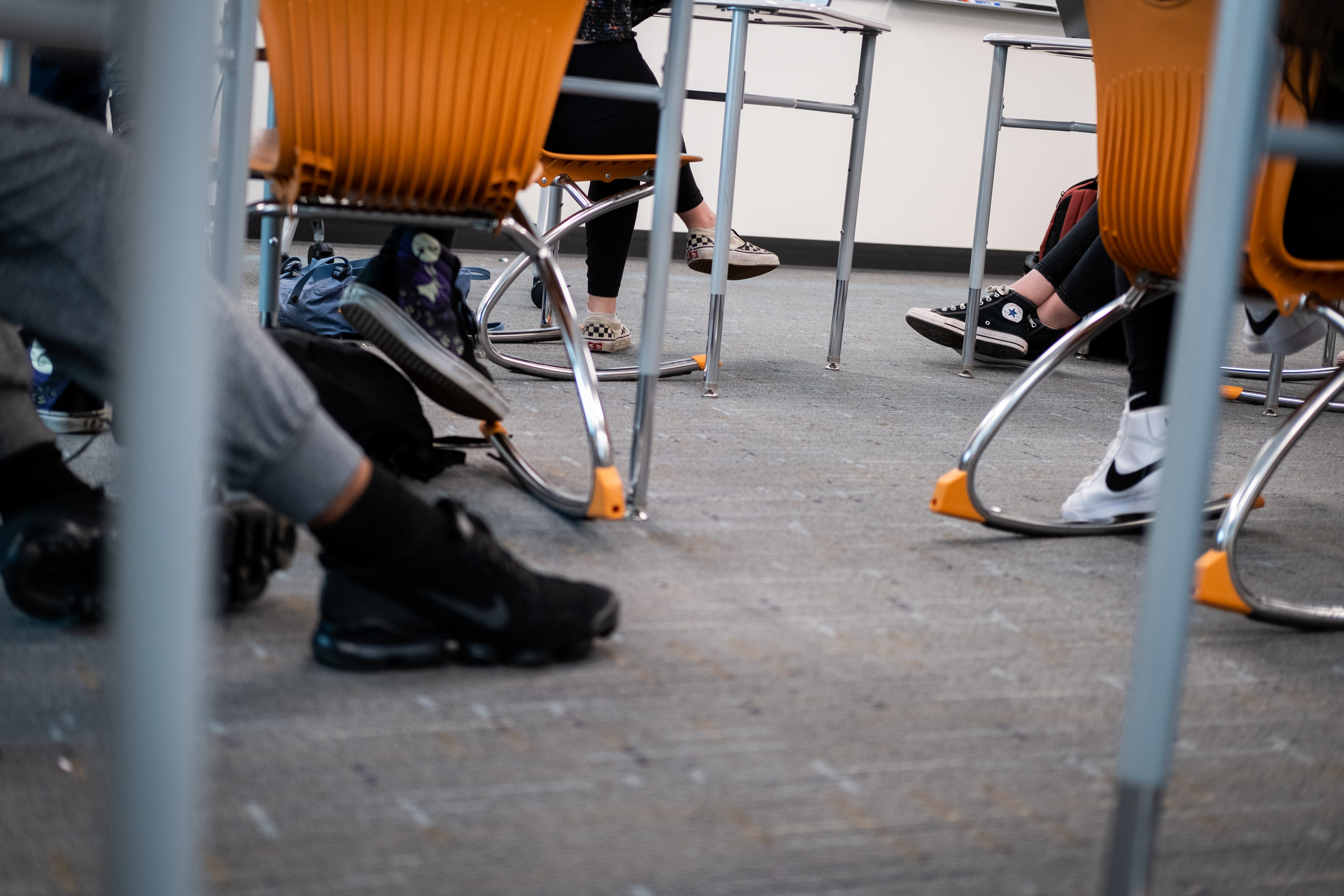 Students' feet beneath their chairs in a classroom.