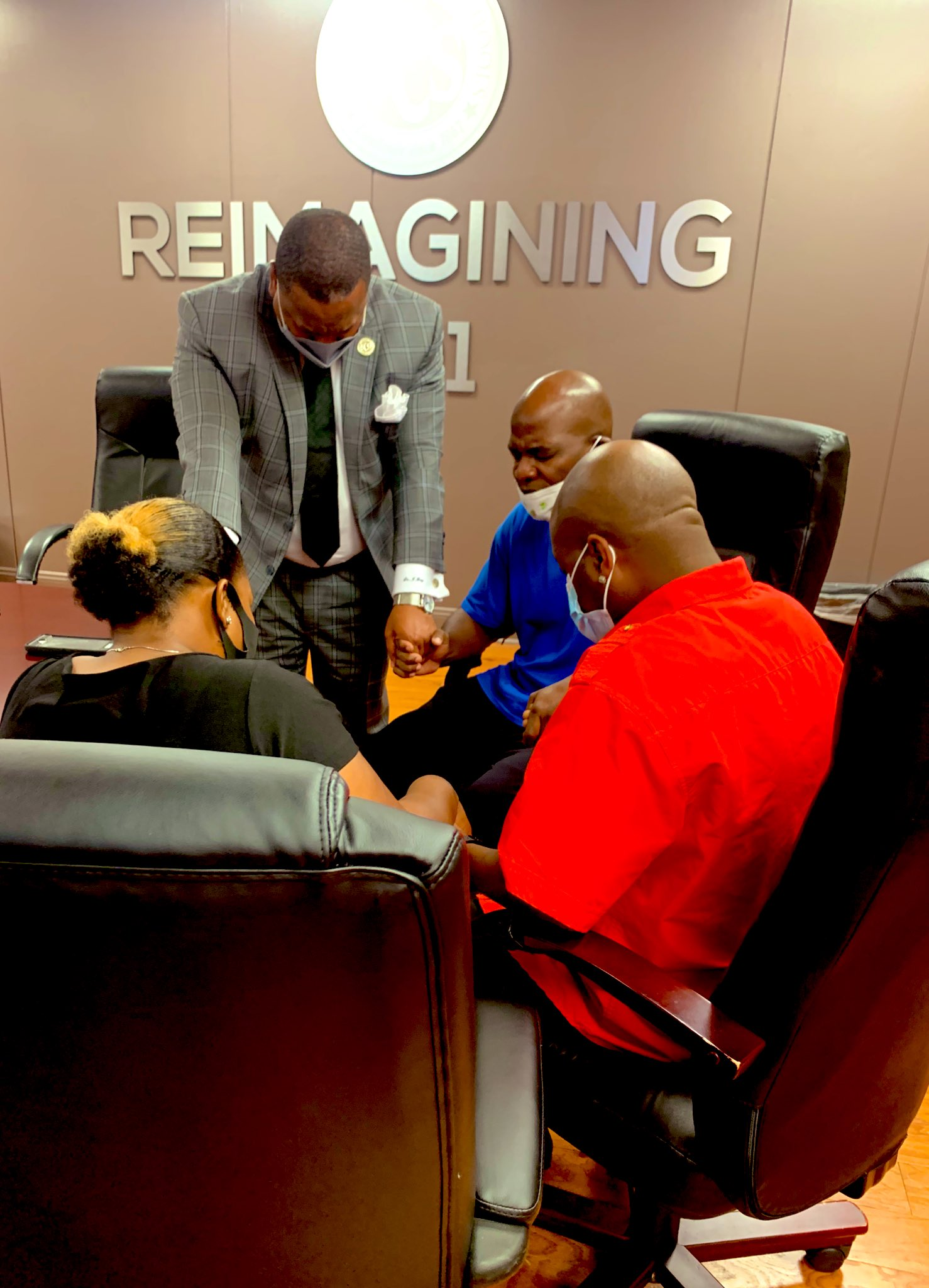Four adults circled together in a conference room hold hands and pray.