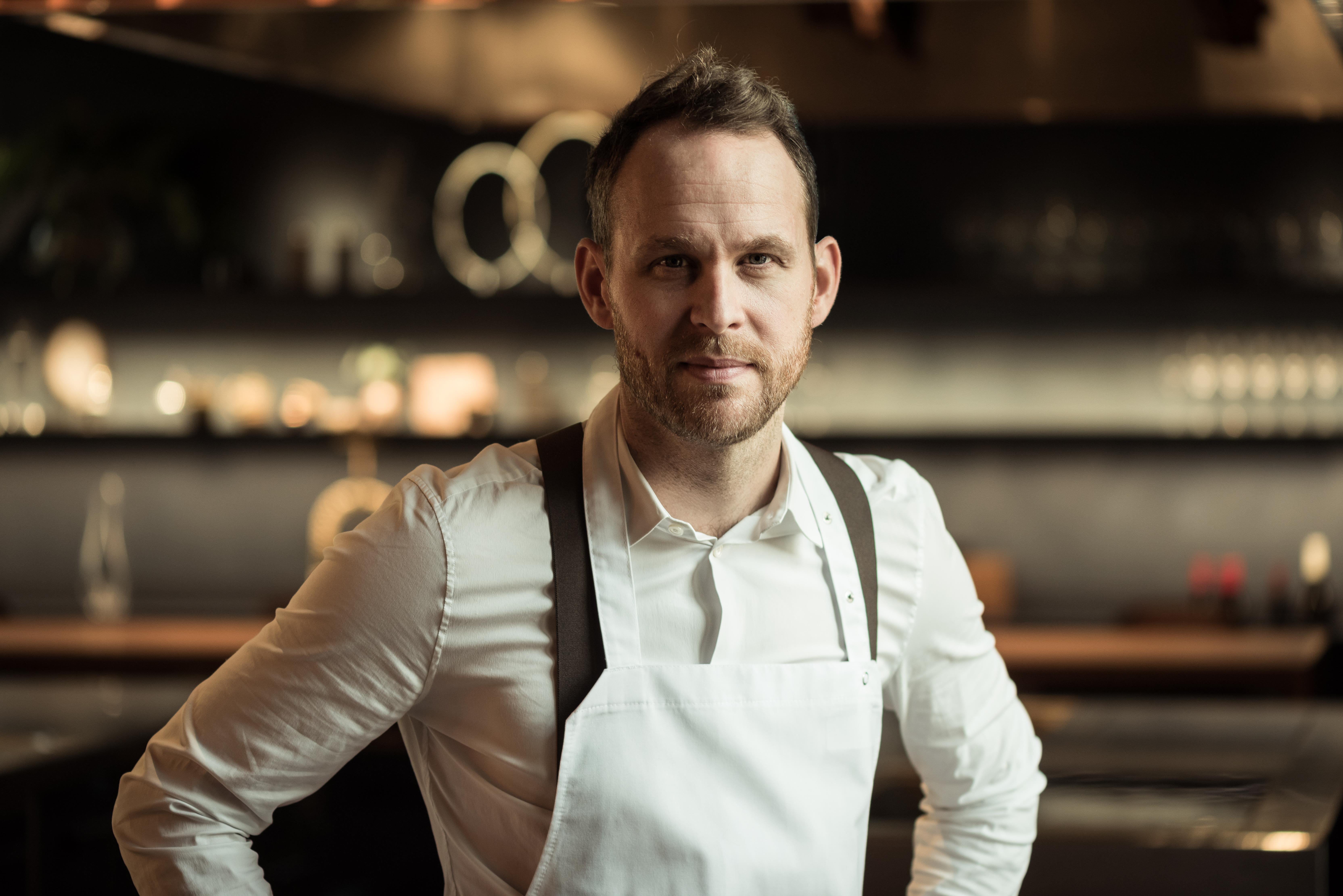 A landscape portrait of chef Bjorn Frantzén, who wears a white shirt and apron.