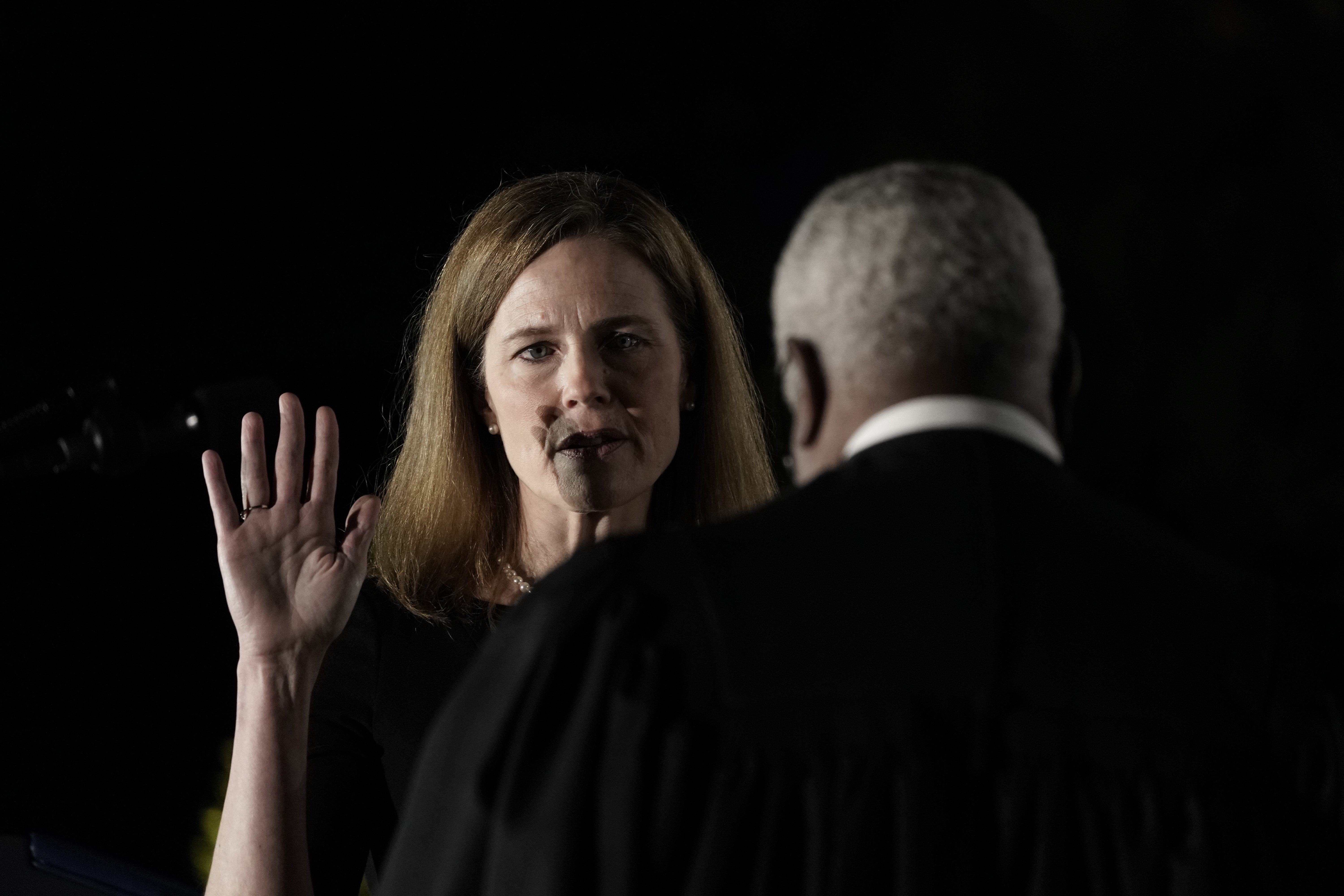 Supreme Court Associate Justice Amy Coney Barrett holding up her hand to take an oath.