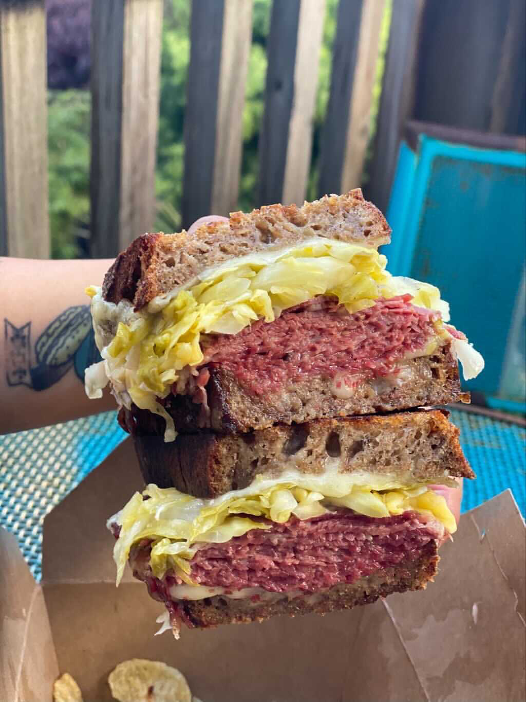 A Reuben sandwich cut in half with a layer of sauerkraut on thick slices of pumpernickel.