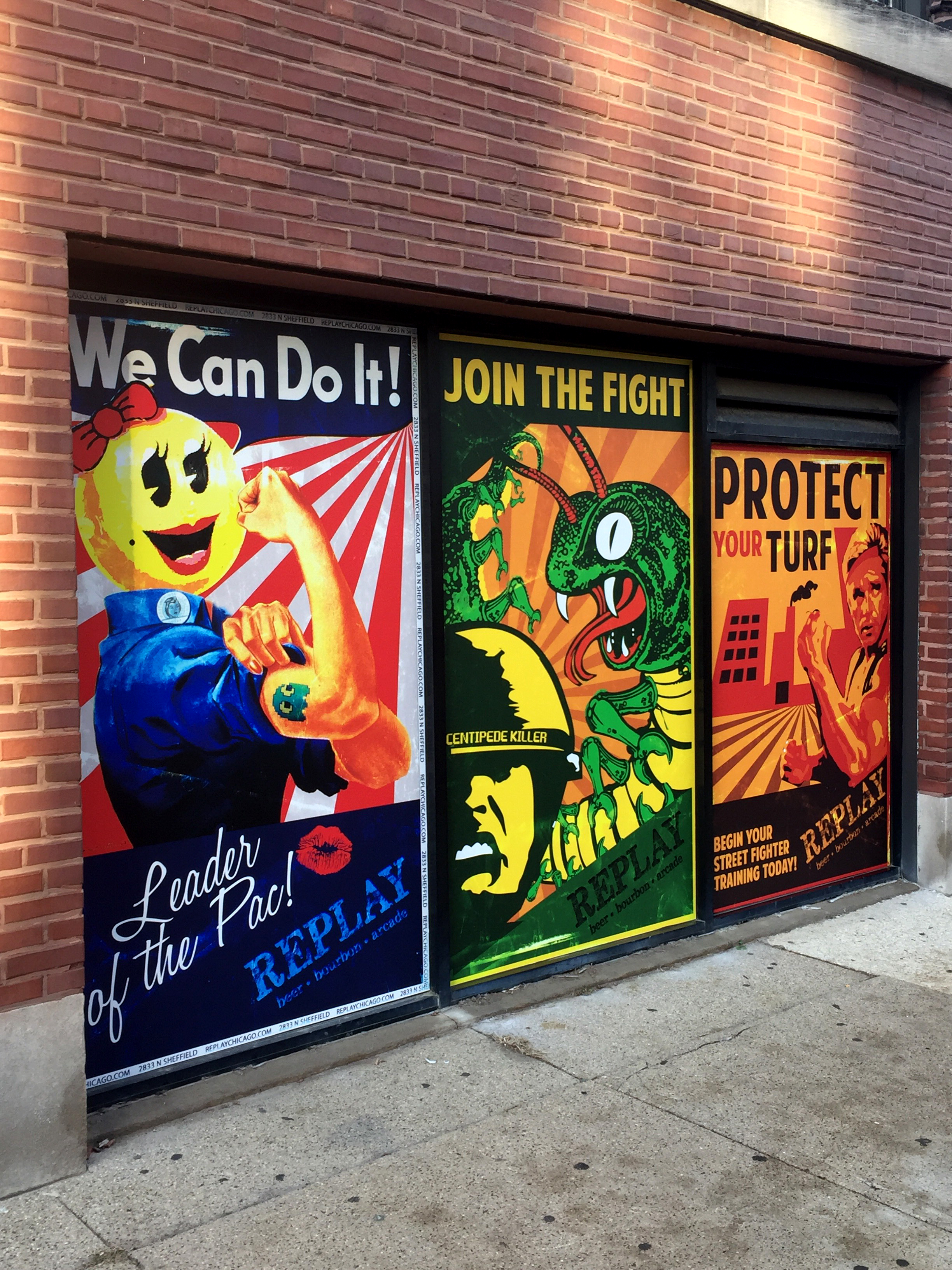 three posters on a brick wall: rosie the riveter with ms. pac-man's head, a centipede attacking a GI, and a soldier in front of a factory