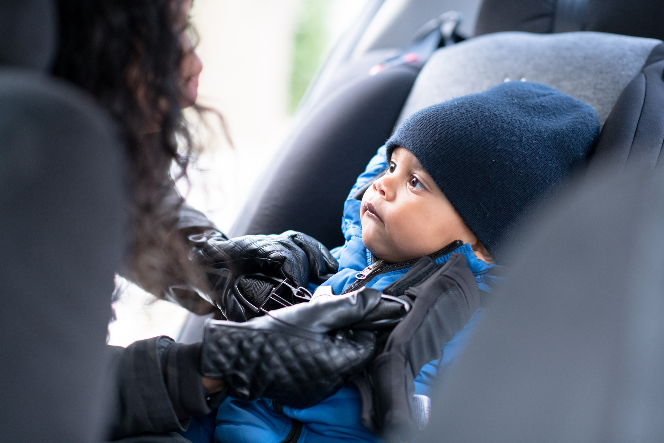 A baby boy with a winter hat sits in in his car seat as his mother buckles him in.