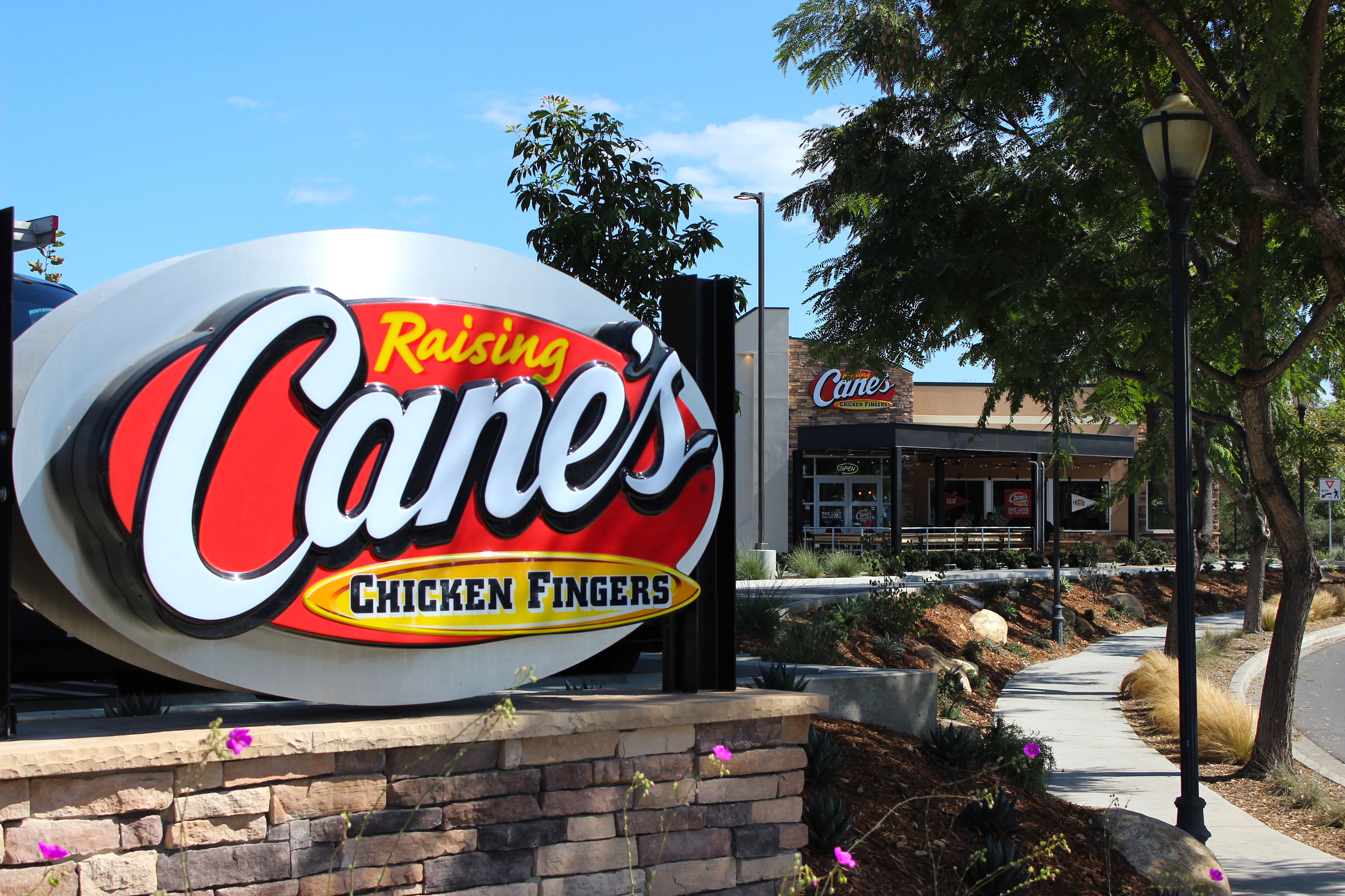 A Raising Cane's sign sits in the forefront of a Raising Cane's restaurant