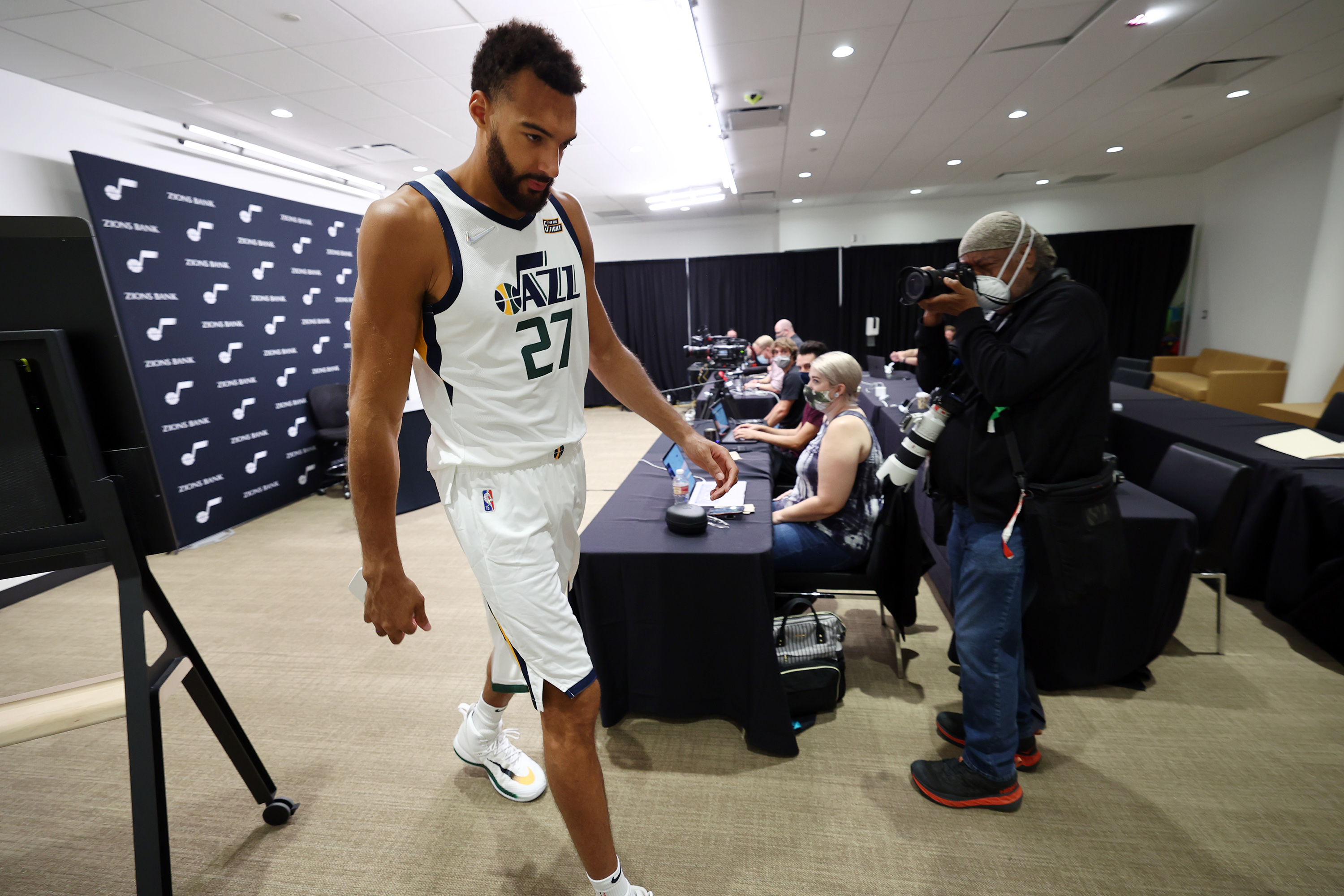 Utah Jazz center Rudy Gobert, wearing a white jersey, exits after an interview during the Utah Jazz media day at Vivint Arena in Salt Lake City.