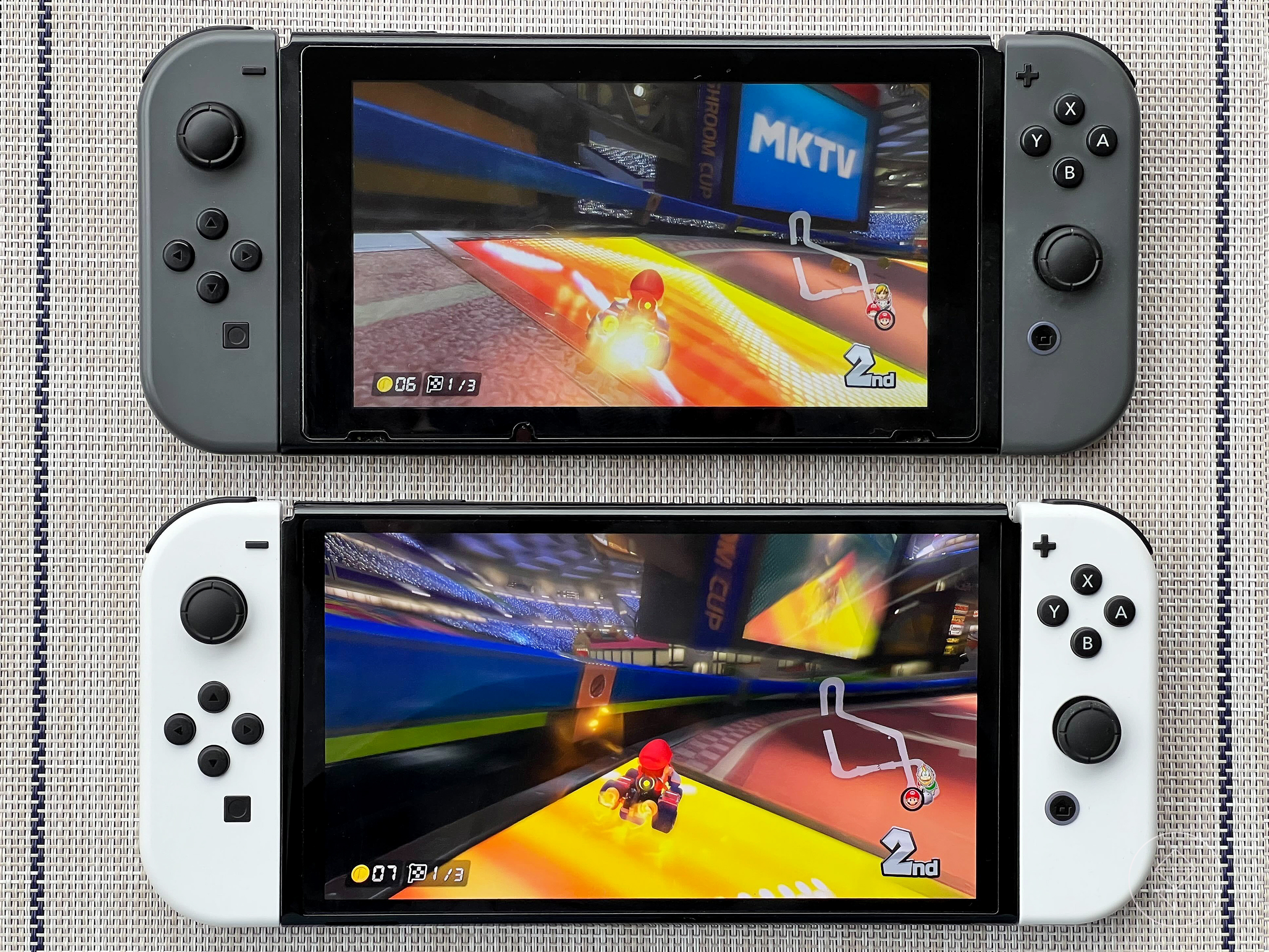 a photo of the original Switch (with dark gray Joy-Cons) above the OLED Switch (with white Joy-Cons), with Mario Kart 8 Deluxe running on both systems