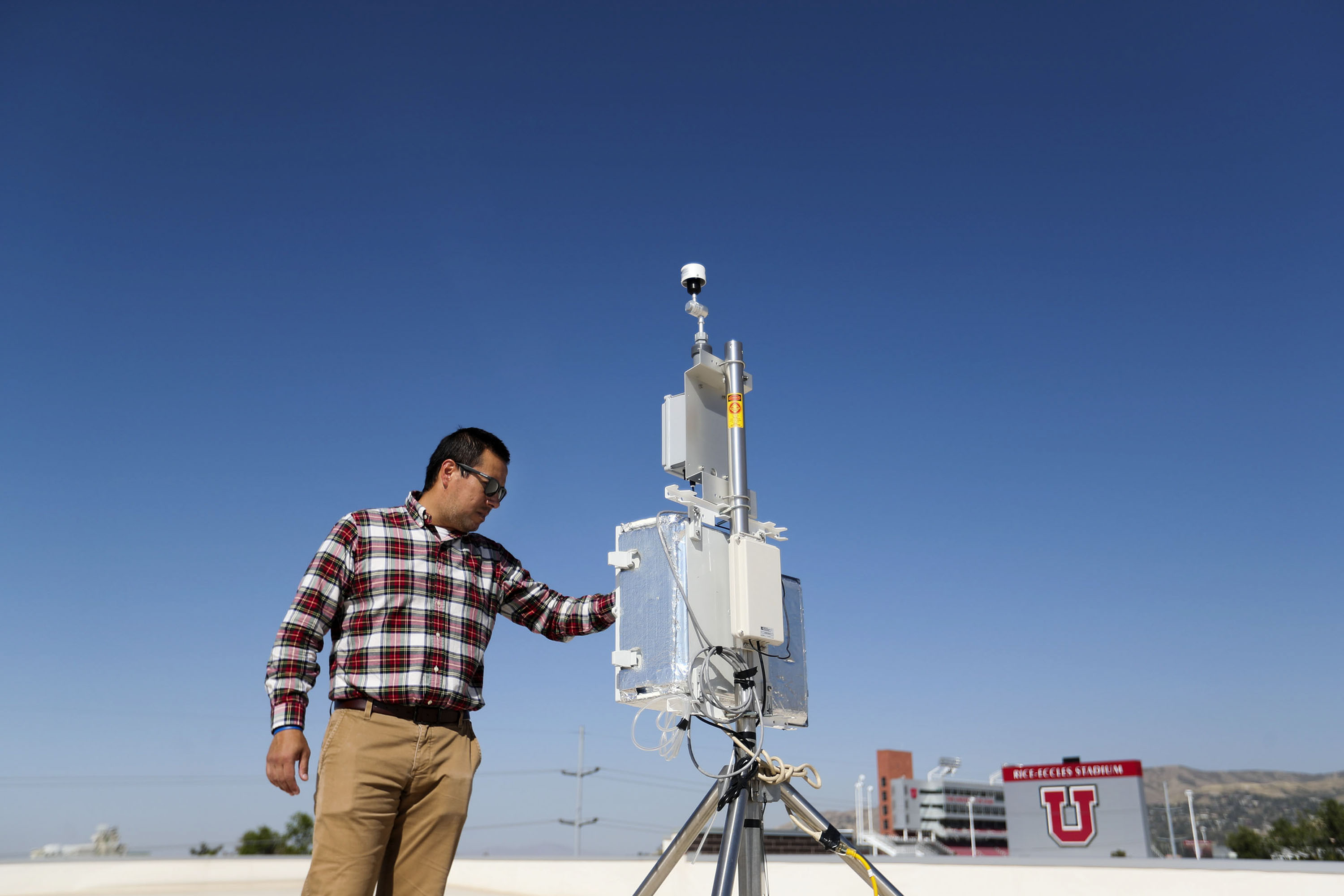 Daniel Mendoza, a professor in atmospheric science, pulmonary medicine and metropolitan planning,checks an air quality monitoring station on the roof of the Spence and Cleone Eccles Football Center at the University of Utah in Salt Lake City on Friday, Sept. 23, 2021.