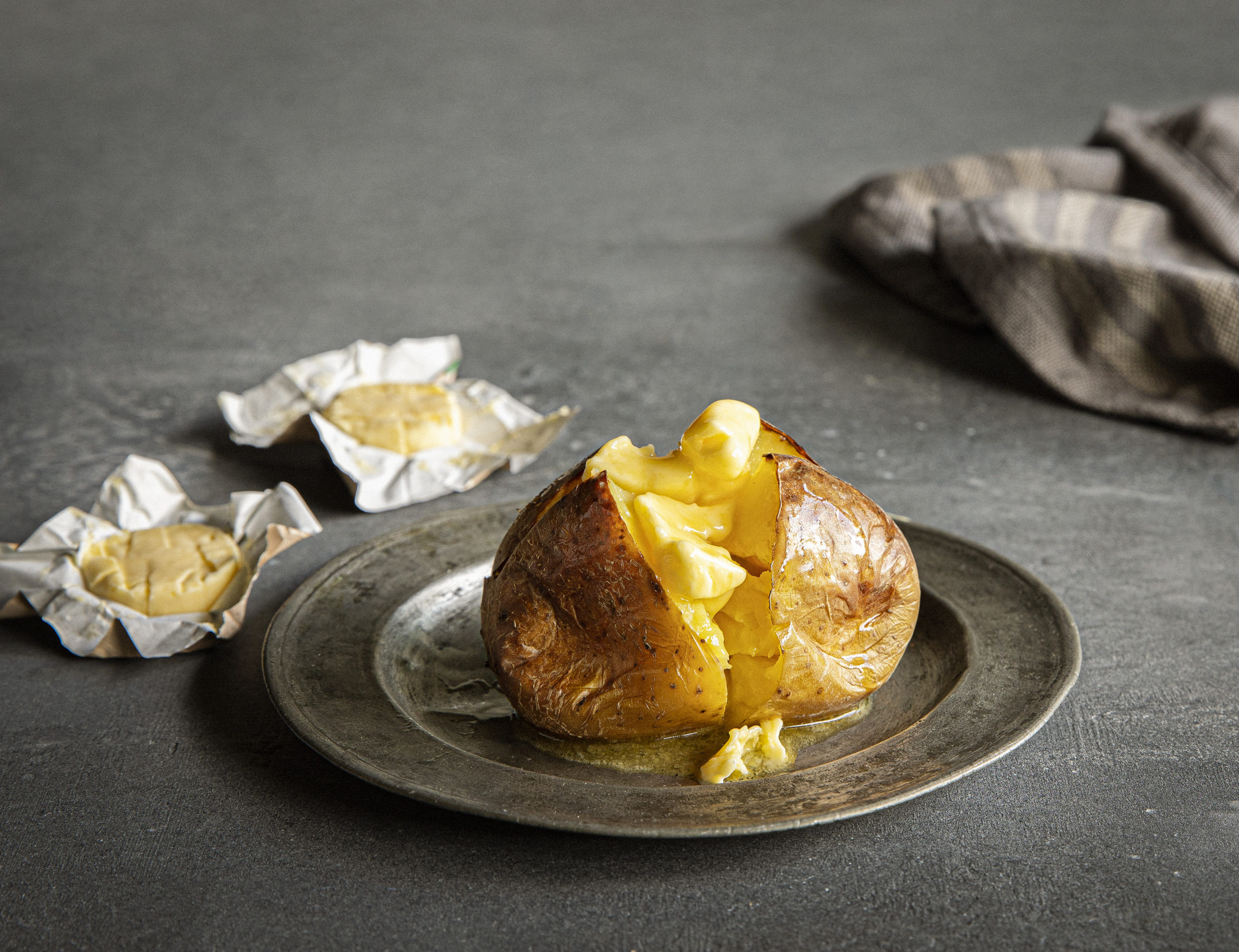 A jacket potato soaked in butter, with butter in the background in its packet.
