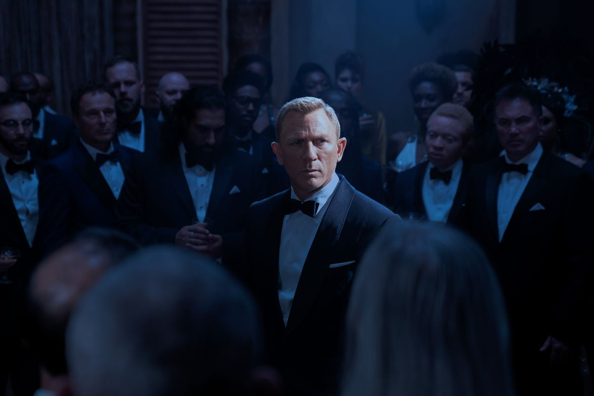 James Bond's face is lit up, while everyone around him is in darkness.