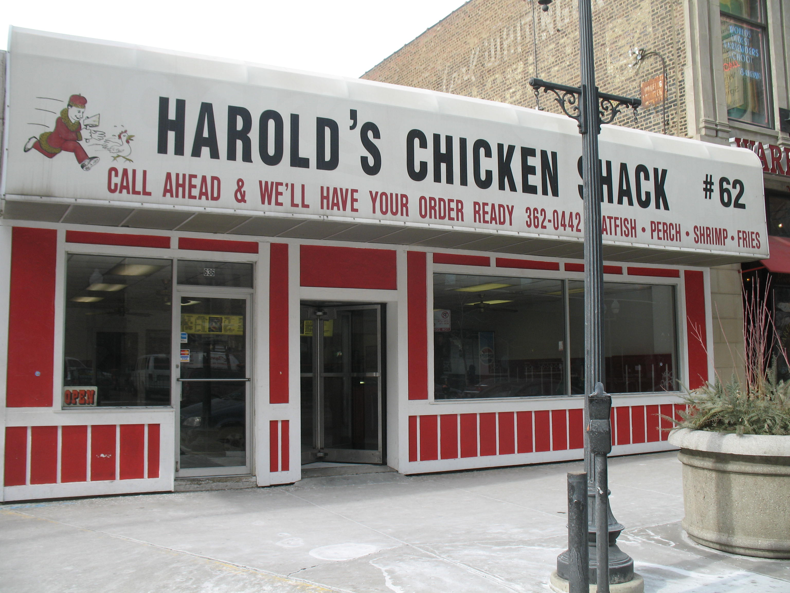 """A restaurant with a red front and a white awning that says """"Harold's Chicken Shack #62"""" with the logo of a man chasing a chicken"""