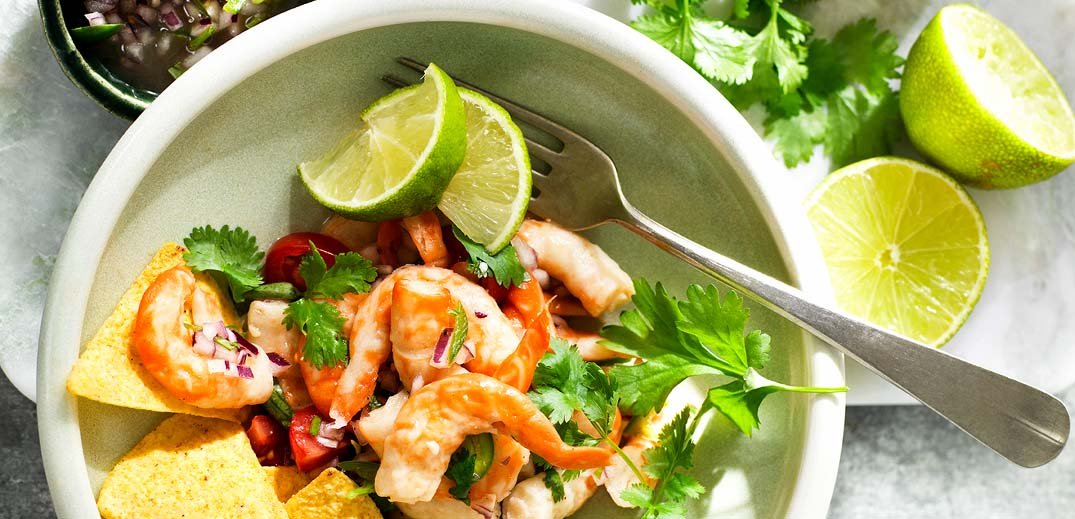 An overhead photo showing a bowl of Nestlé's imitation shrimp product, Vrimp, with tortilla chips and lime wedges.