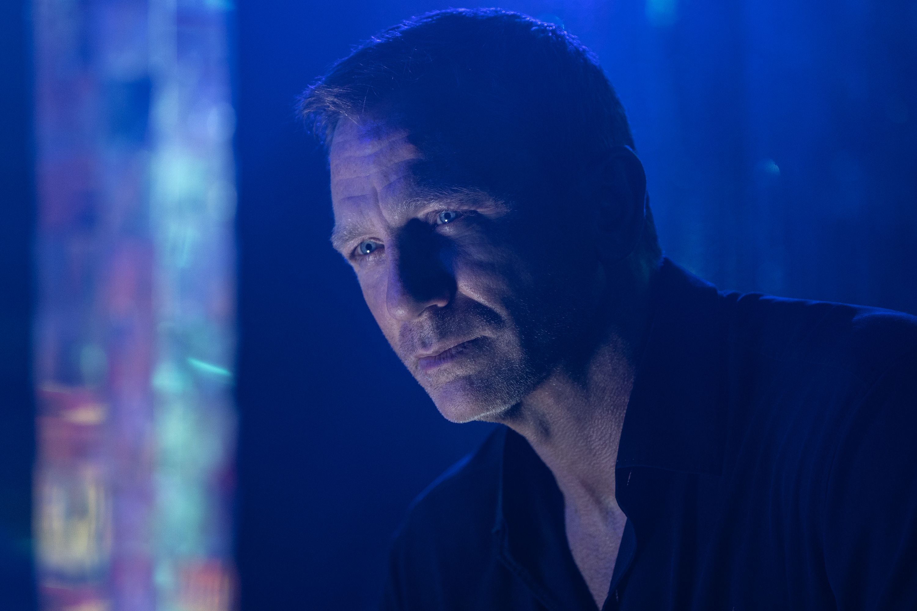 Daniel Craig looks broody in blue light in No Time To Die (to be fair, he looks broody everywhere, but this is specifically an image description, not a character description)