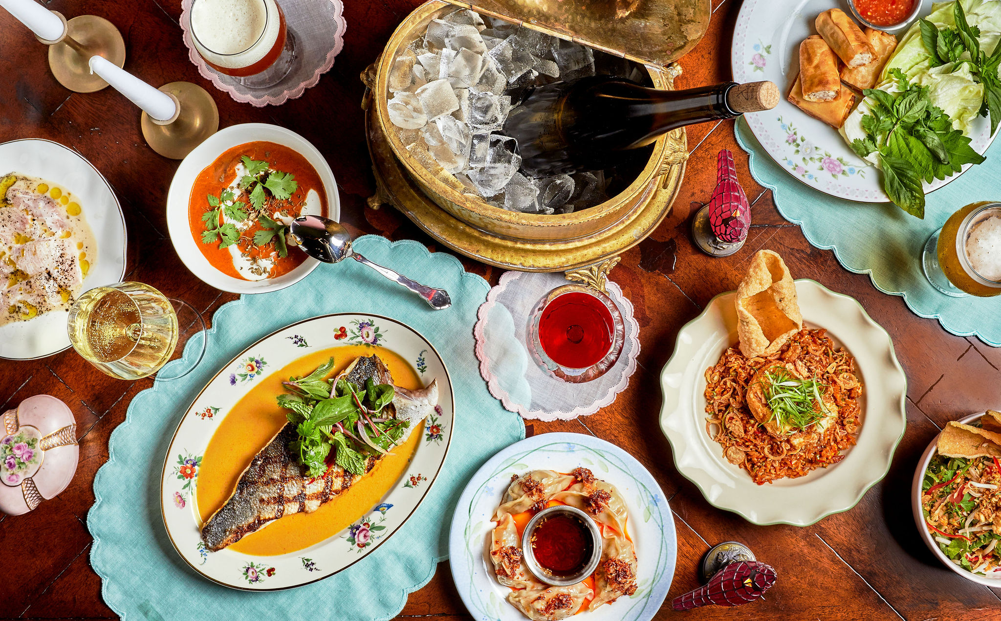 Dishes from Cobi's at Dhaba in Santa Monica laid out with colorful plates and a wood table.