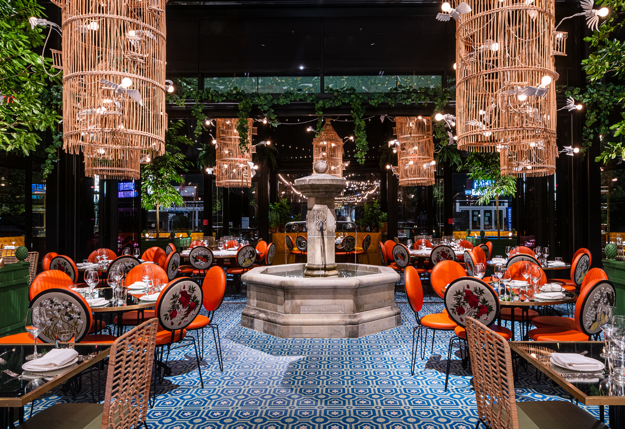 A stone fountain sits in the center of an Ilili dining room with daisy blue tile floors and huge wicker baskets hanging from the ceiling.