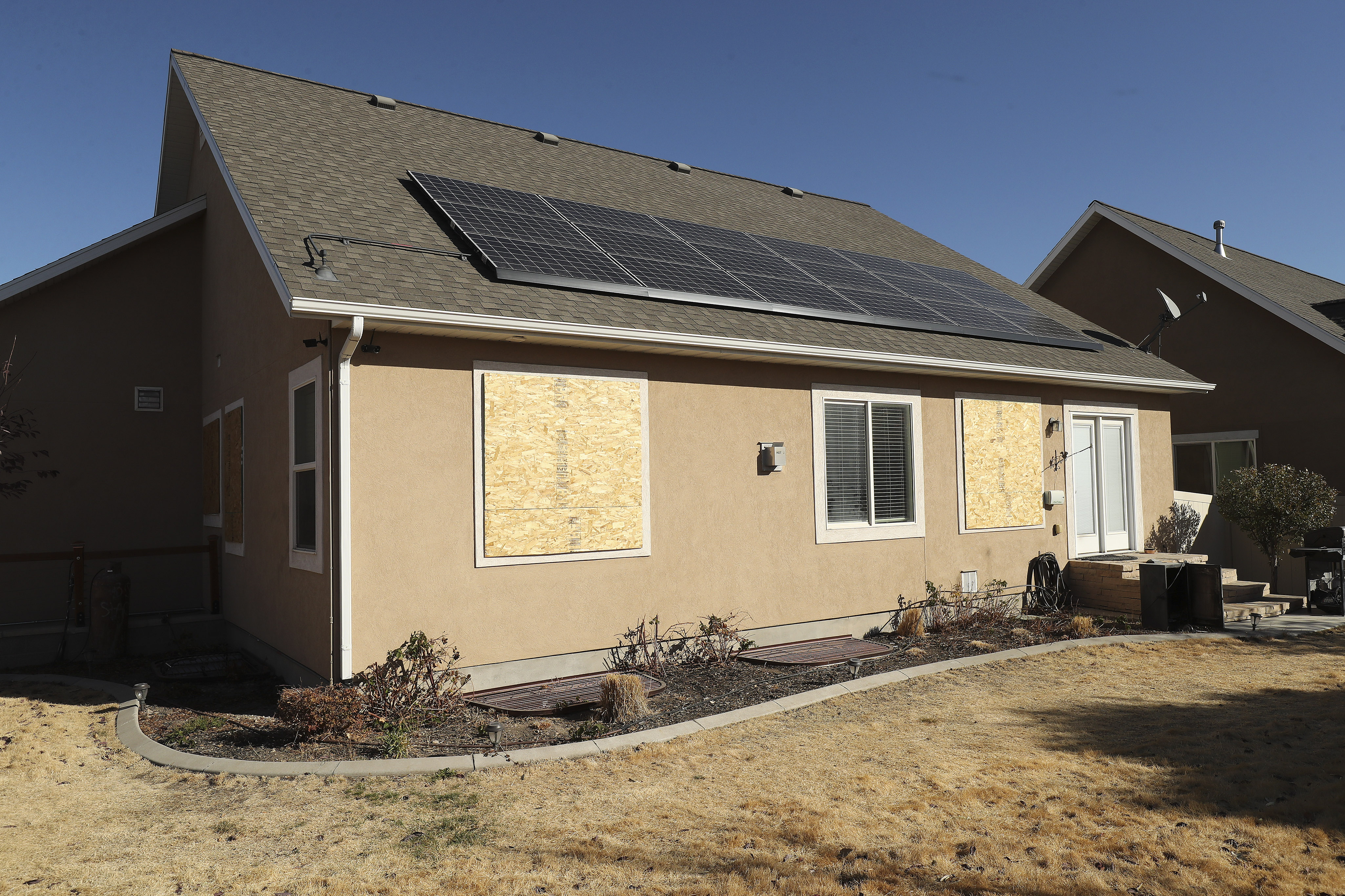 The windows of a house on Snow Moon Place in South Jordan are boarded up on Sunday, Nov. 1, 2020.