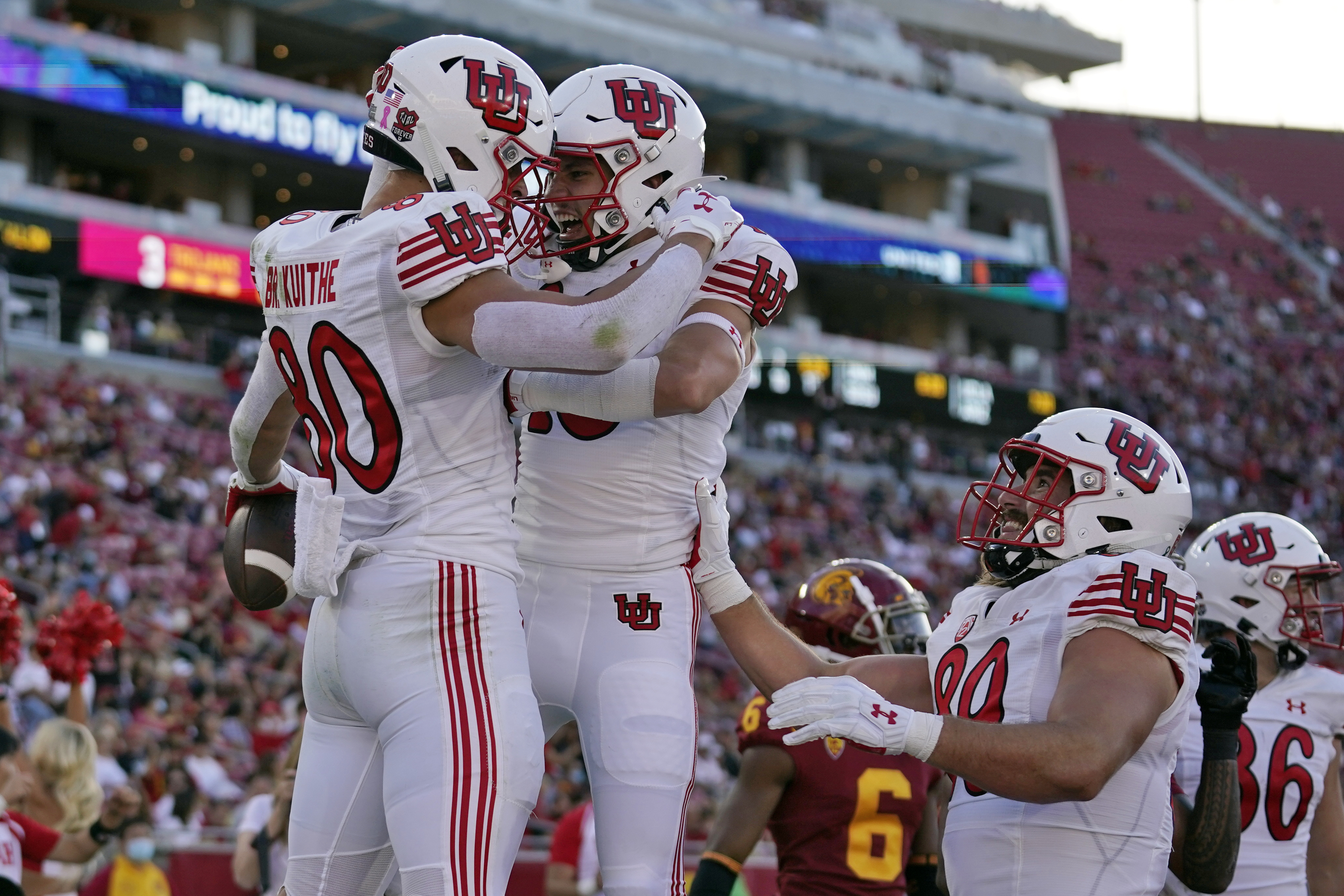 Utah tight end Brant Kuithe, wearing a white helmet and jersey, celebrates his touchdown with wide receiver Britain Covey