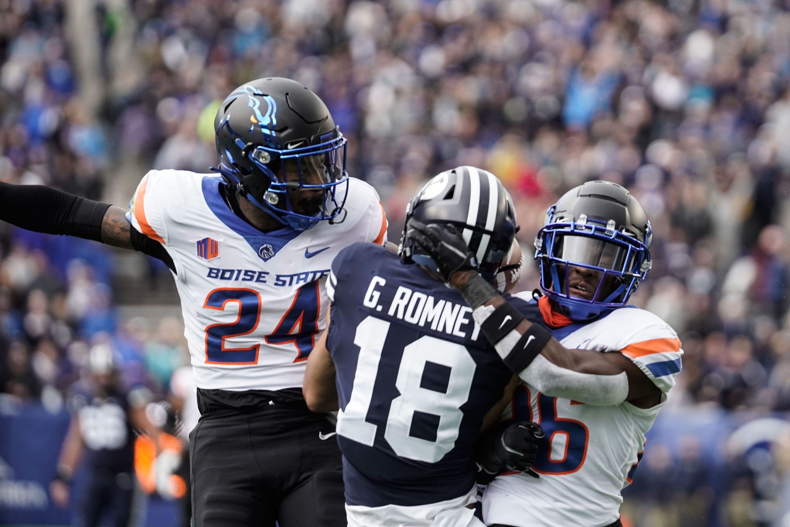 BYU wide receiver Gunner Romney is defended by Boise State's Damon Cole (24) and Jared Reed during an NCAA college football game at LaVell Edwards Stadium in Provo on Saturday, Oct. 9, 2021.