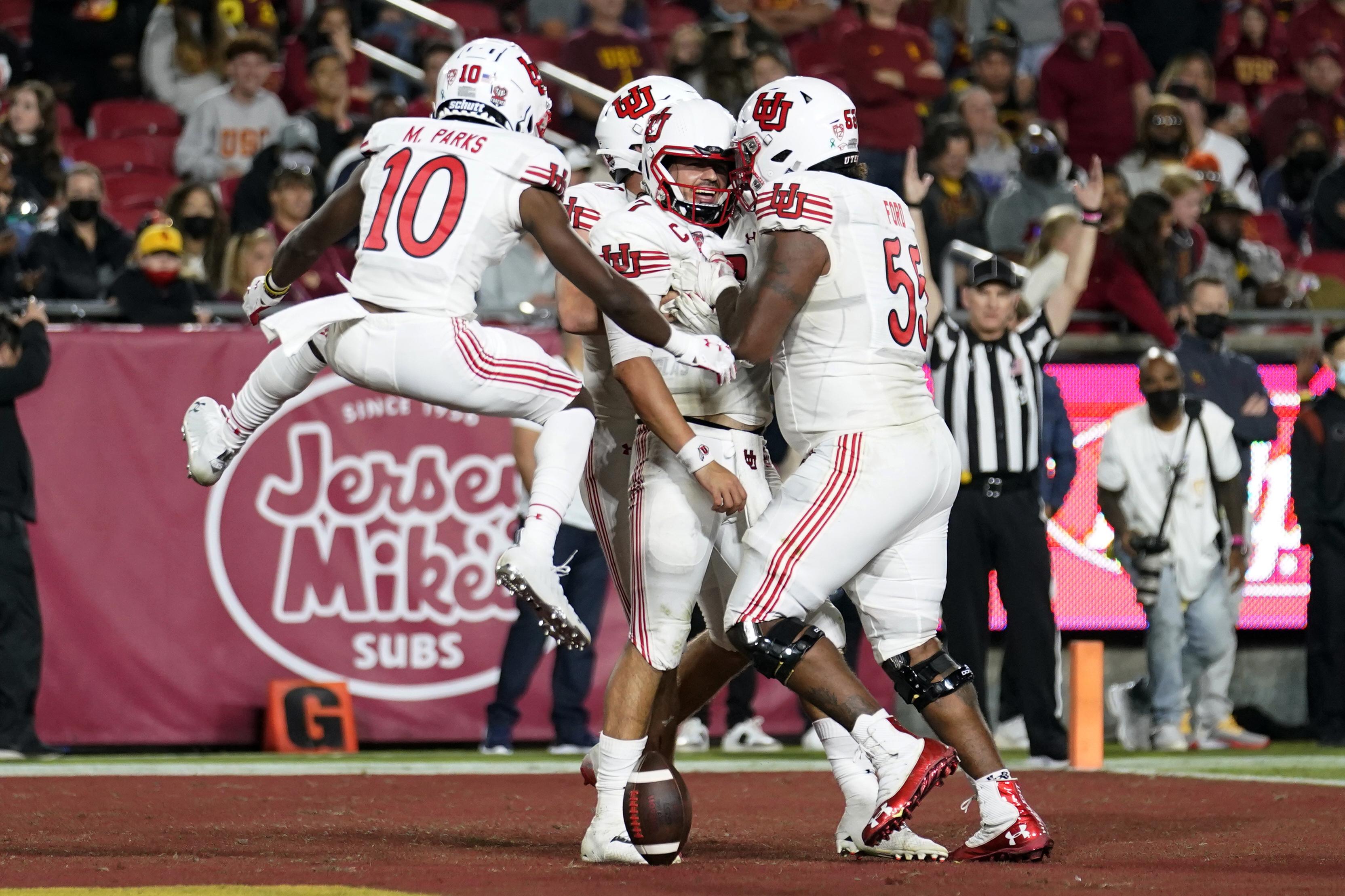 Utah quarterback Cameron Rising jumps up to celebrates his rushing touchdown with teammates.
