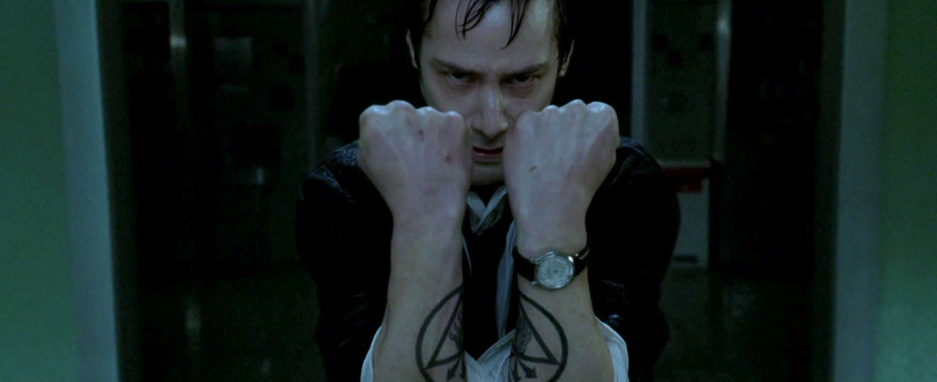A wet Constantine holds up his two arms to form a rune tattoo