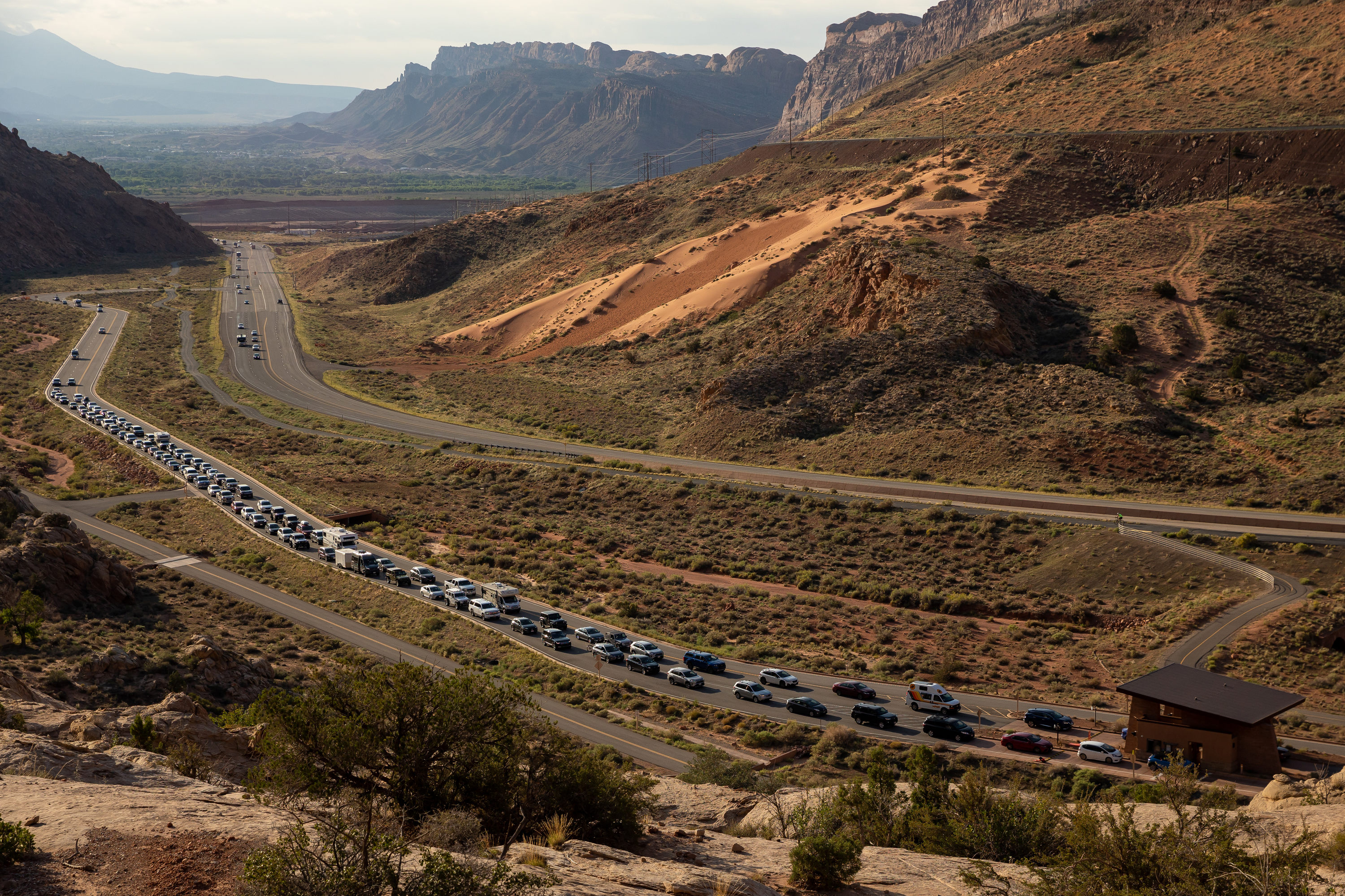 The entrance road to Arches National Park outside Moab begins to back up with visitors on Sunday, Sept. 19, 2021.
