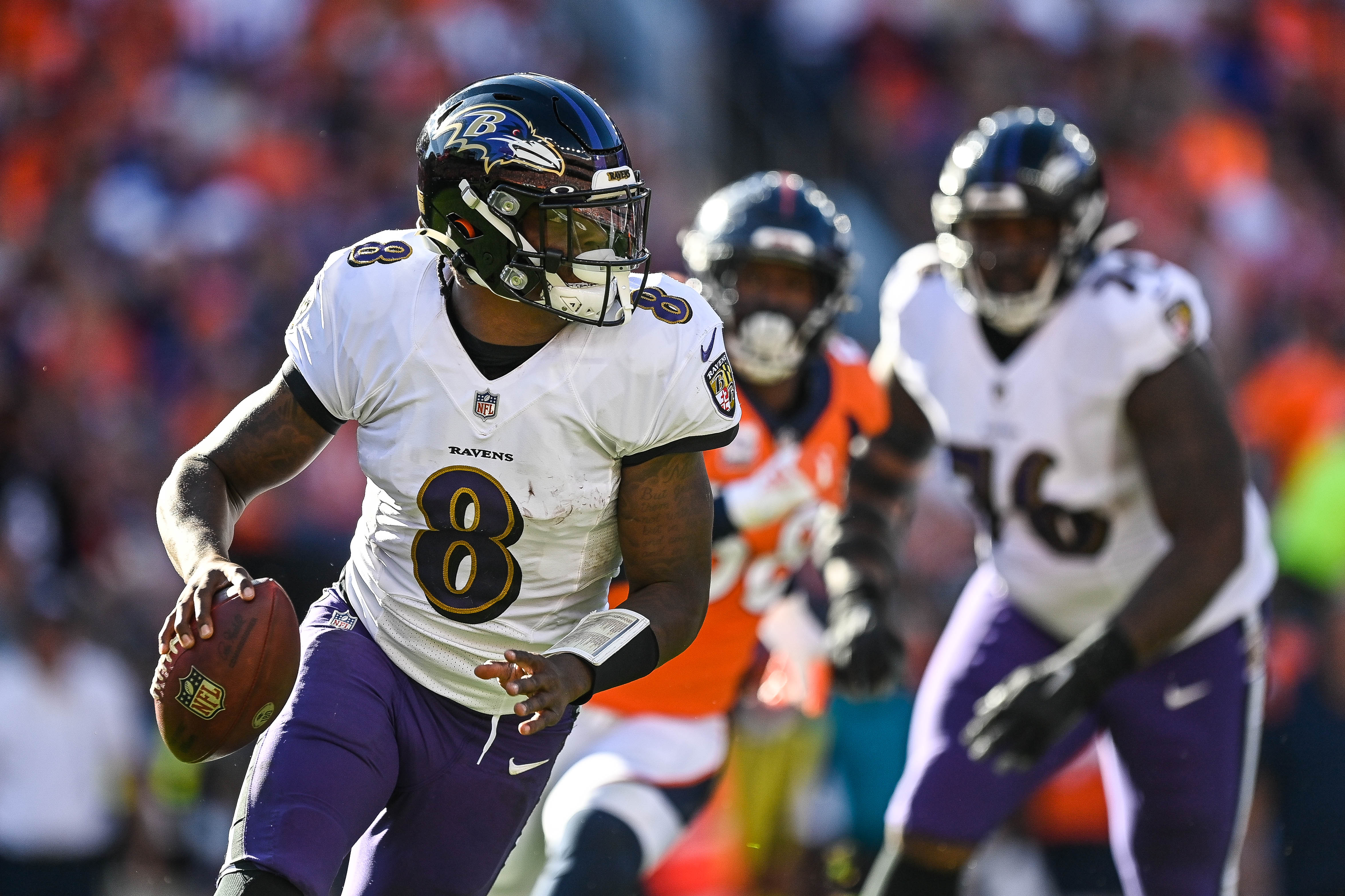 Lamar Jackson #8 of the Baltimore Ravens rolls out of the pocket in the third quarter of a game against the Denver Broncos at Empower Field at Mile High on October 3, 2021 in Denver, Colorado.