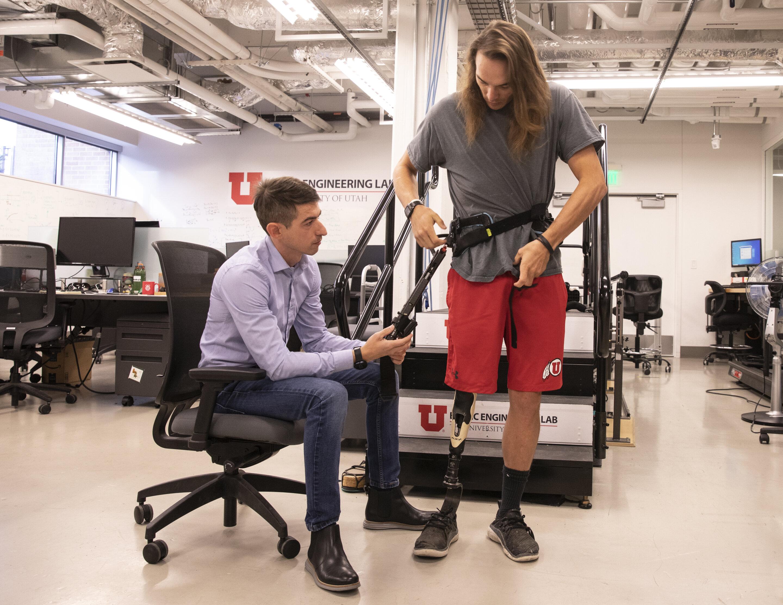 University of Utah assistant professor Tommaso Lenzi helps Alec McMorris put on an experimental exoskeleton.