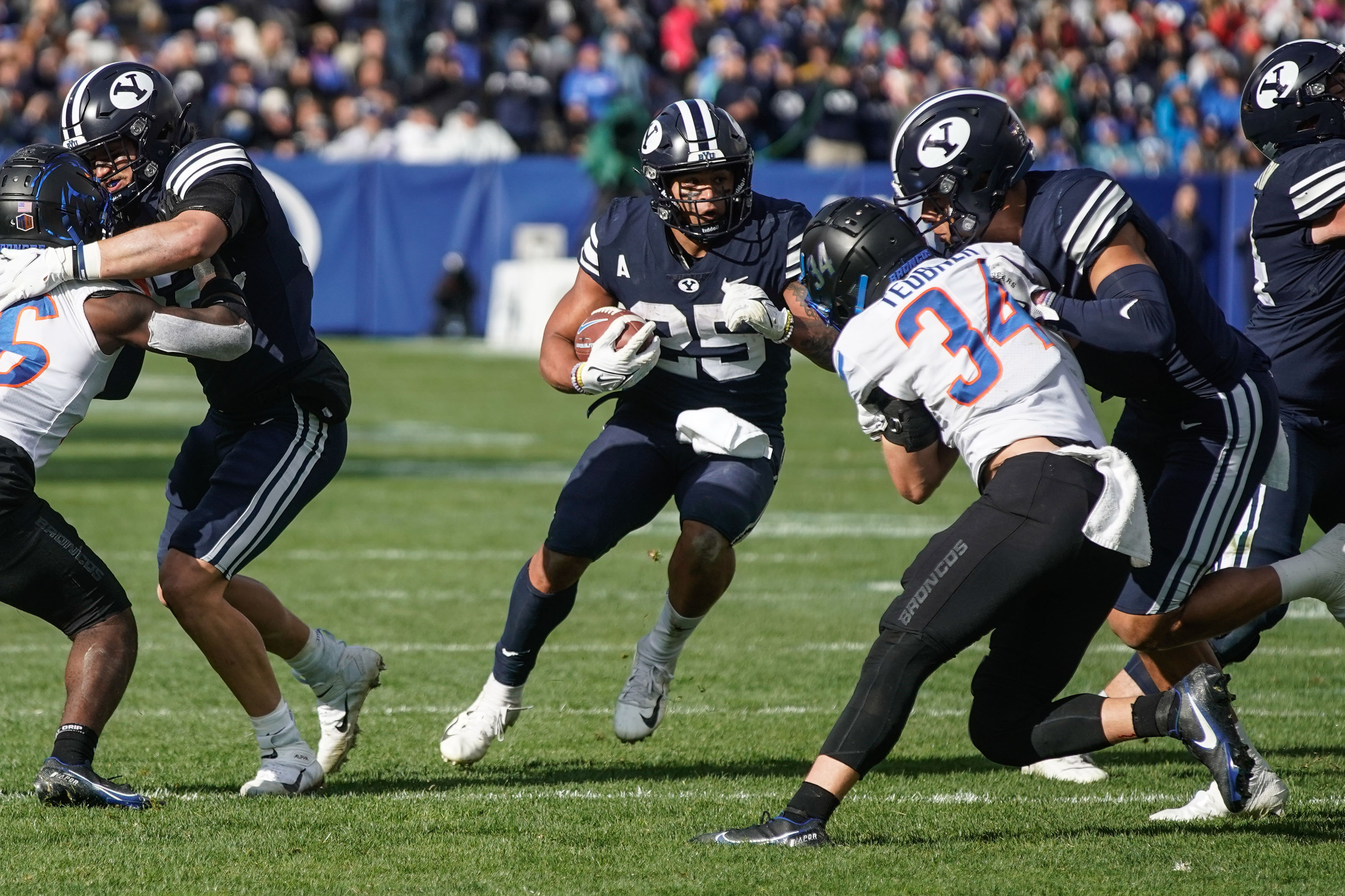 BYU running back Tyler Allgeier (25) runs past Boise State defenders for a touchdown during an NCAA college football game.