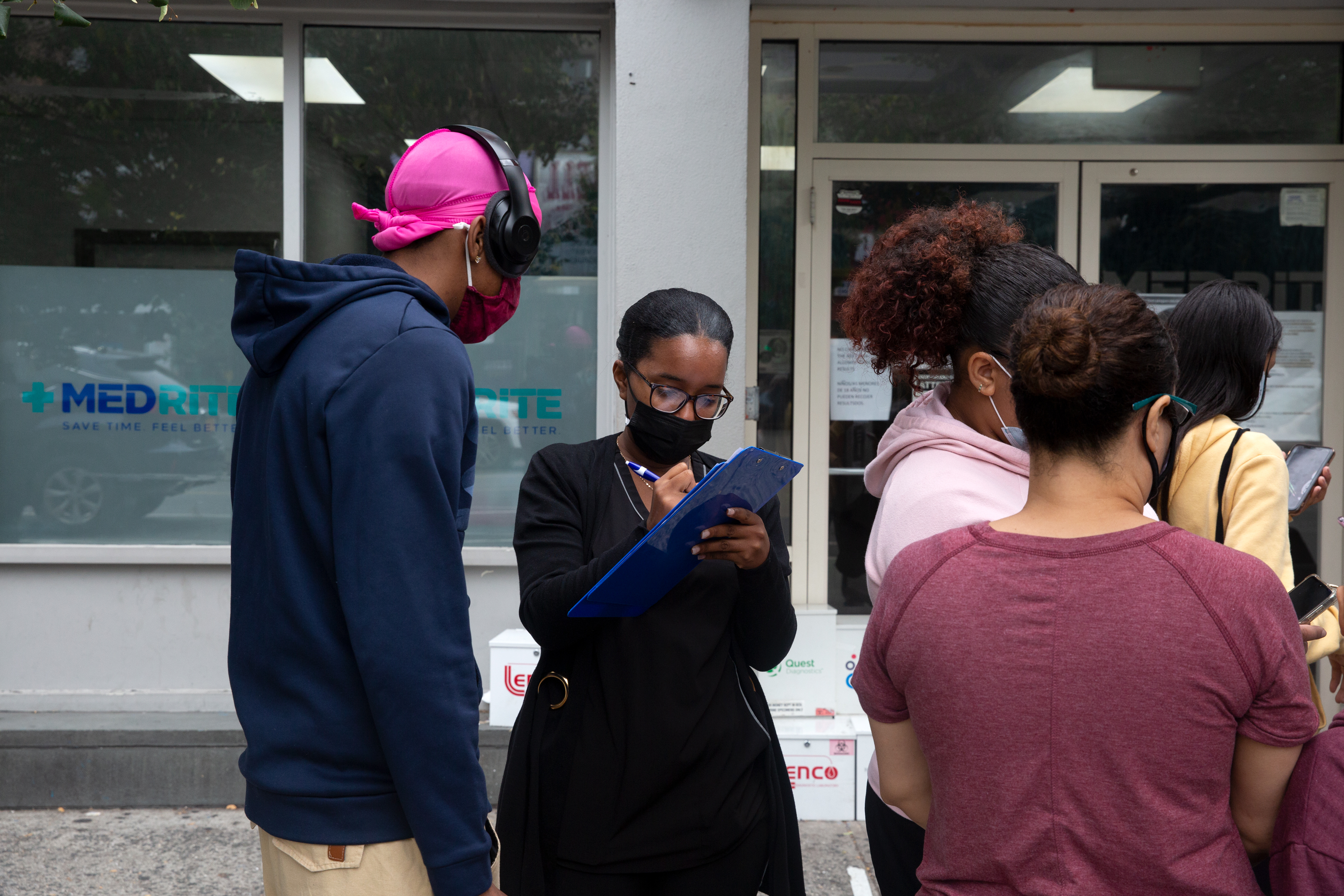 A health care worker signs people in outside an urgent care COVID testing site on Dyckman Street in Inwood, Oct. 6, 2021.