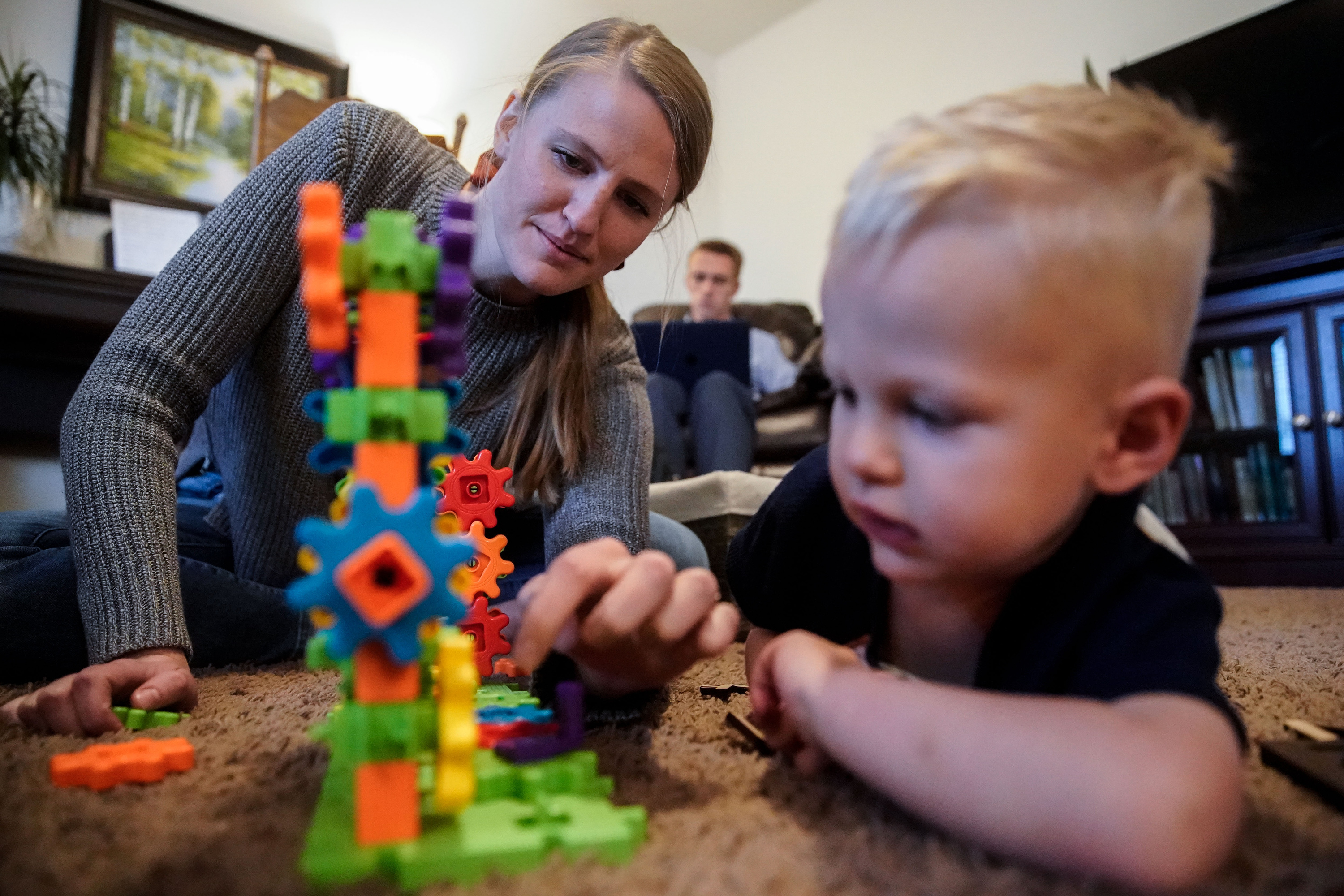 Elissa George plays with her son Tanner, 2, as her husband Austen George works in the background at their house in Provo on Friday, Oct. 8, 2021.