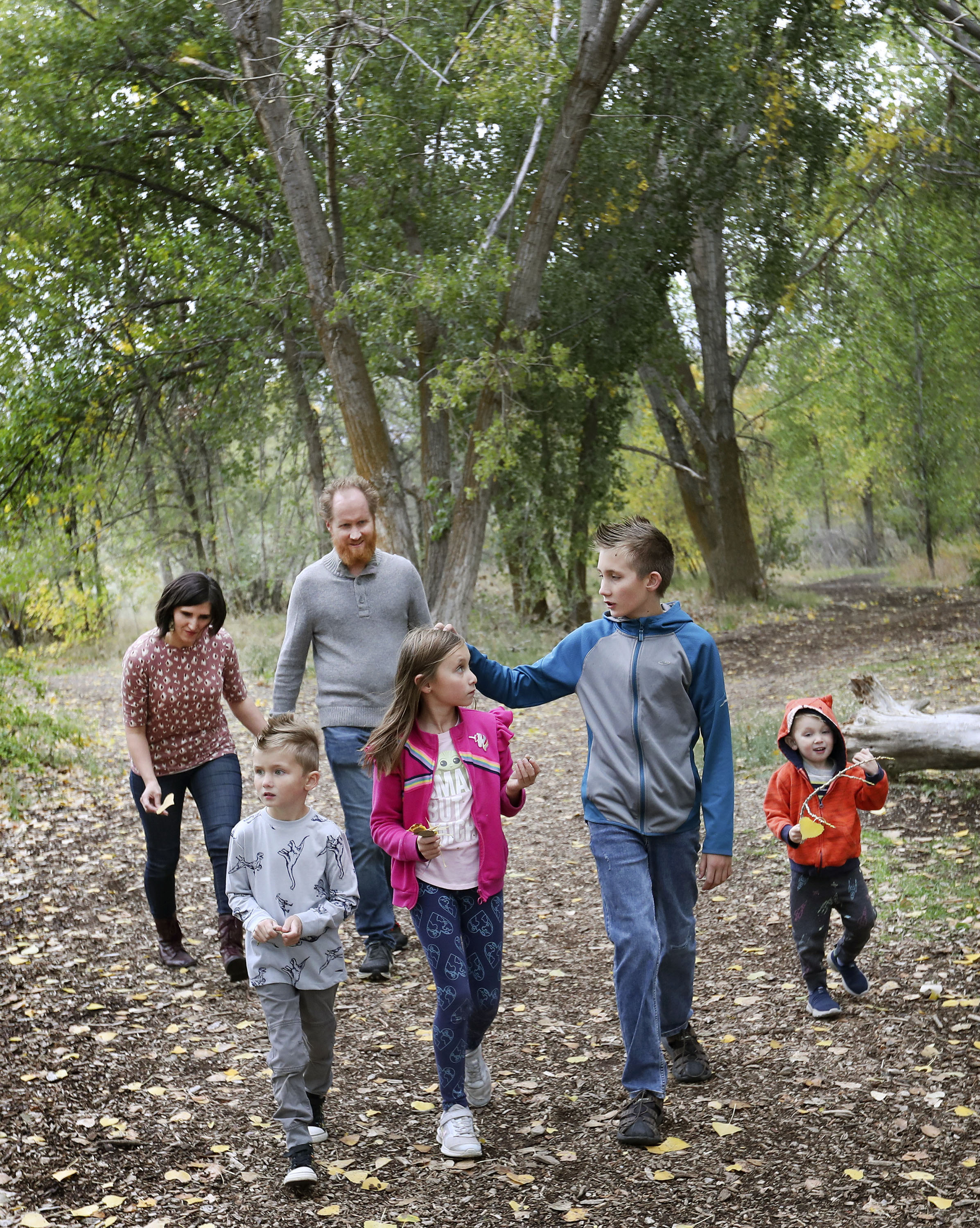 Melanie and Sam Jewkes walk with their children, left to right, Nico, Sapphire, Winston and Flint, near their home in Murray on Friday, Oct. 8, 2021.