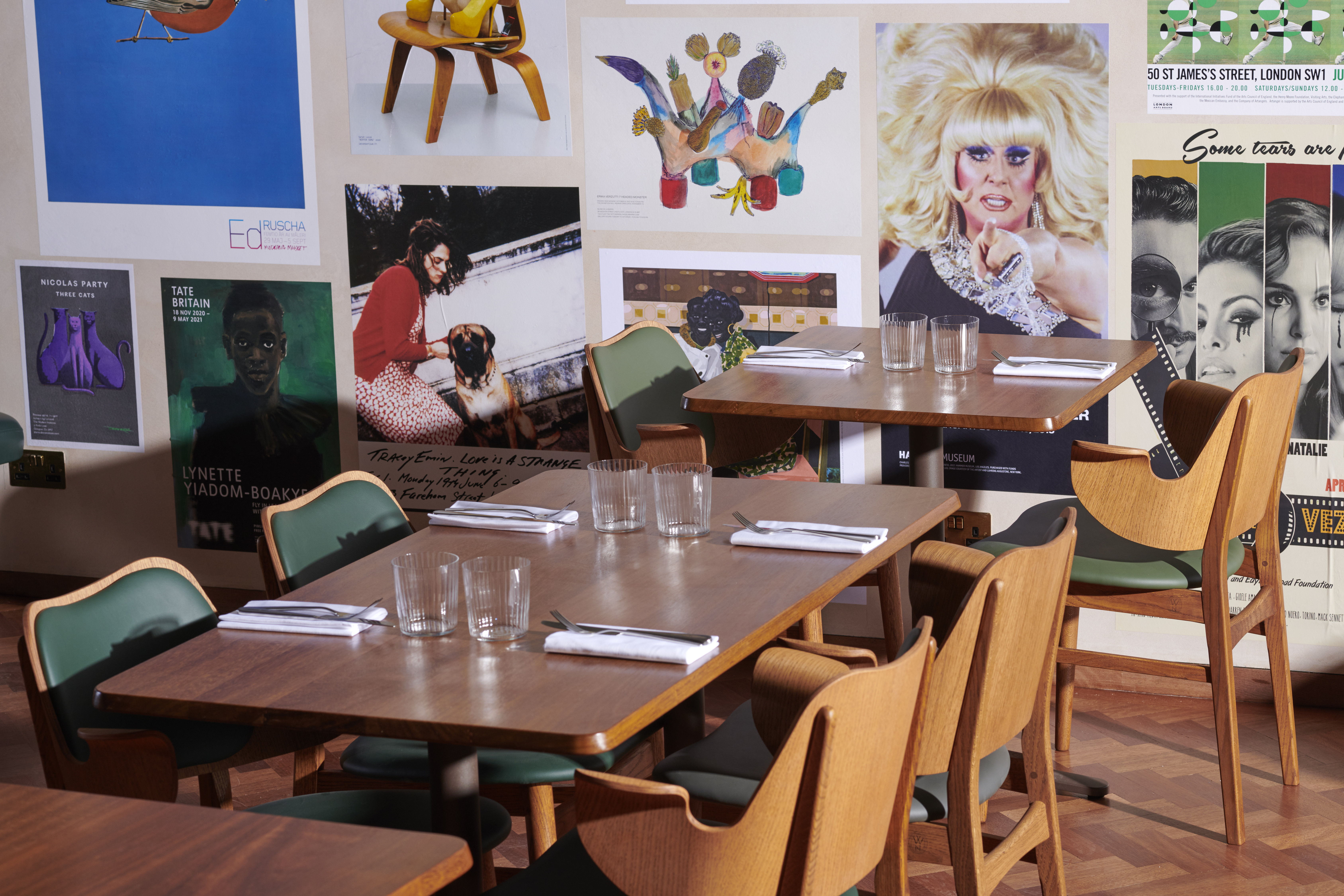 A dining room of mid-century / Bauhaus tables and chairs, with short tumbler glasses and white napkins on each table. The backdrop is a selection of art posters, creating a collage effect on the wall.
