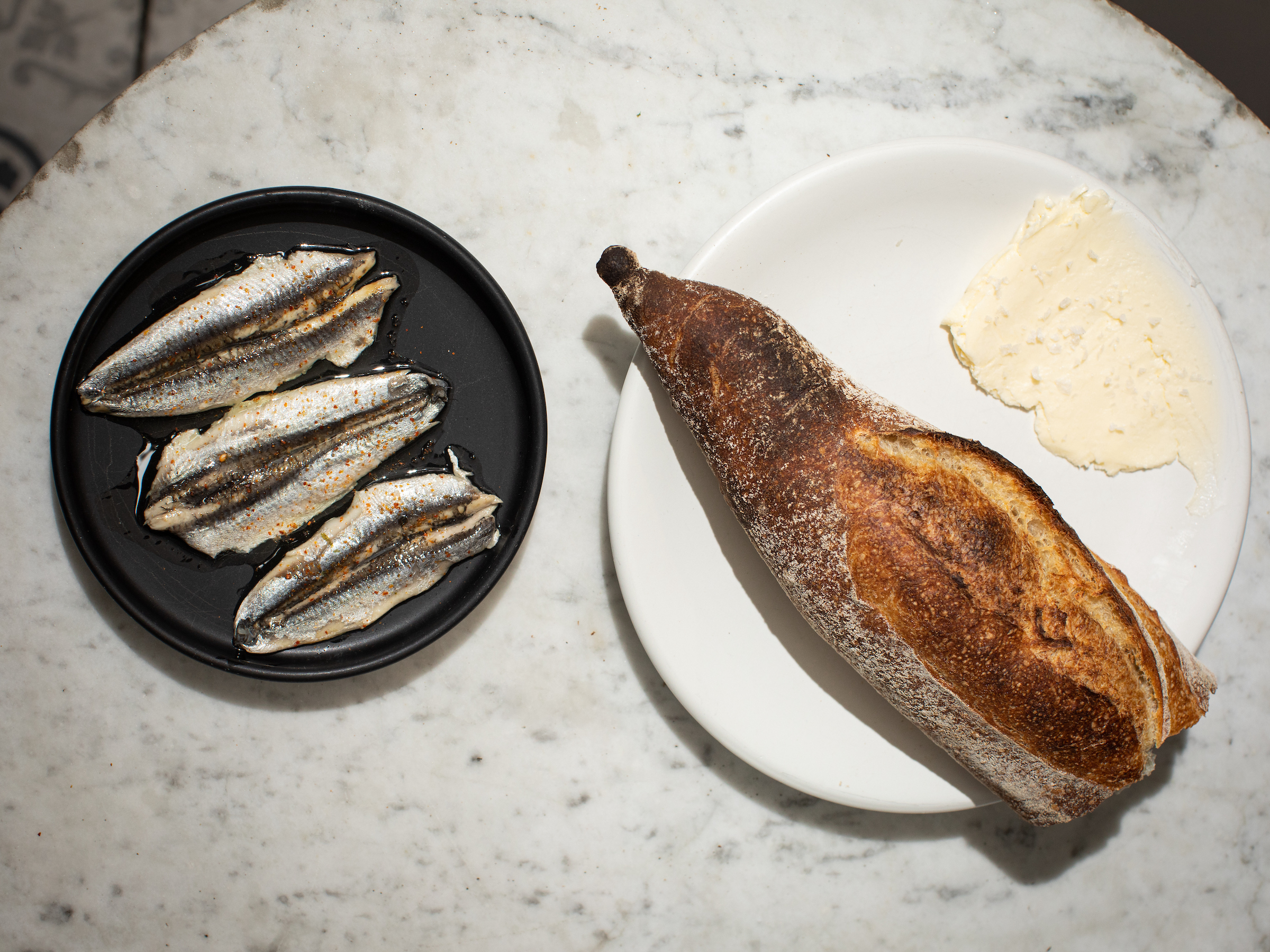 An overhead photograph of two plates, one with three fish filets and another with a baguette and smear of butter