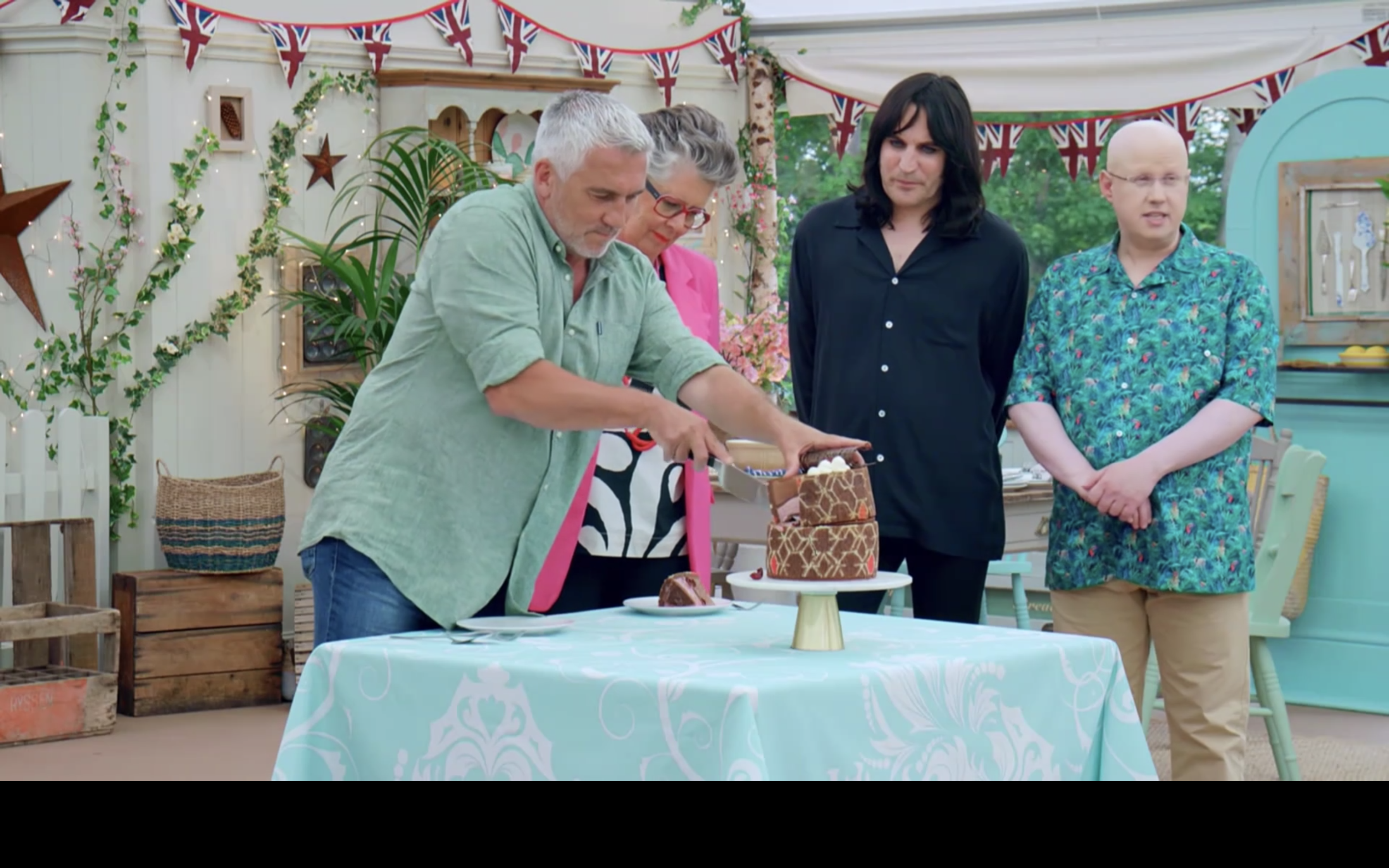 Paul Hollywood cuts into an imprimé dessert, patterned like European tiling, surrounded by Prue Leith, Noel Fielding, and Matt Lucas.